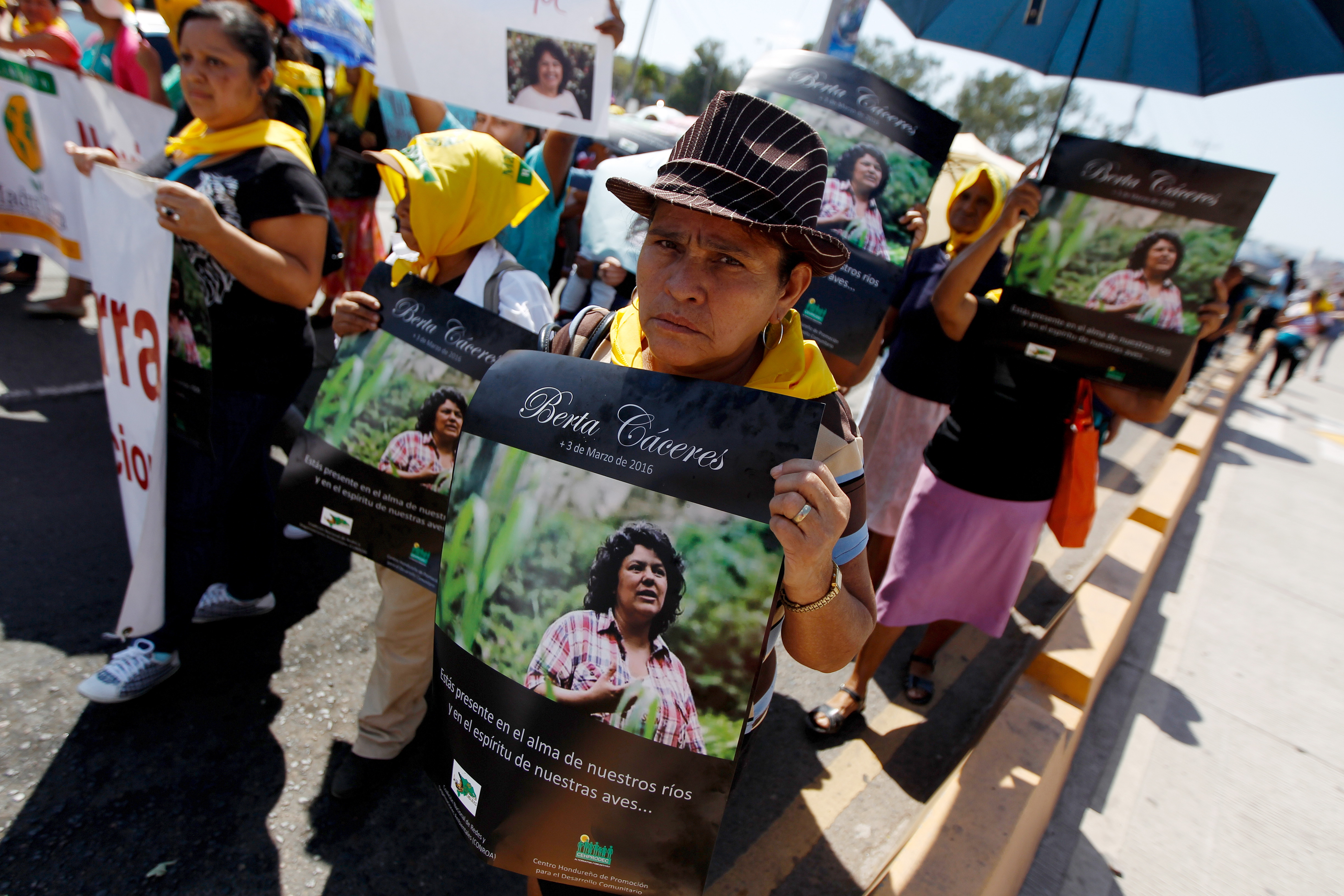 An indigenous woman holds a poster with a photograph of slain environmental rights activist Berta Caceres during a march to demand justice in Tegucigalpa, Honduras, March 16, 2016.
