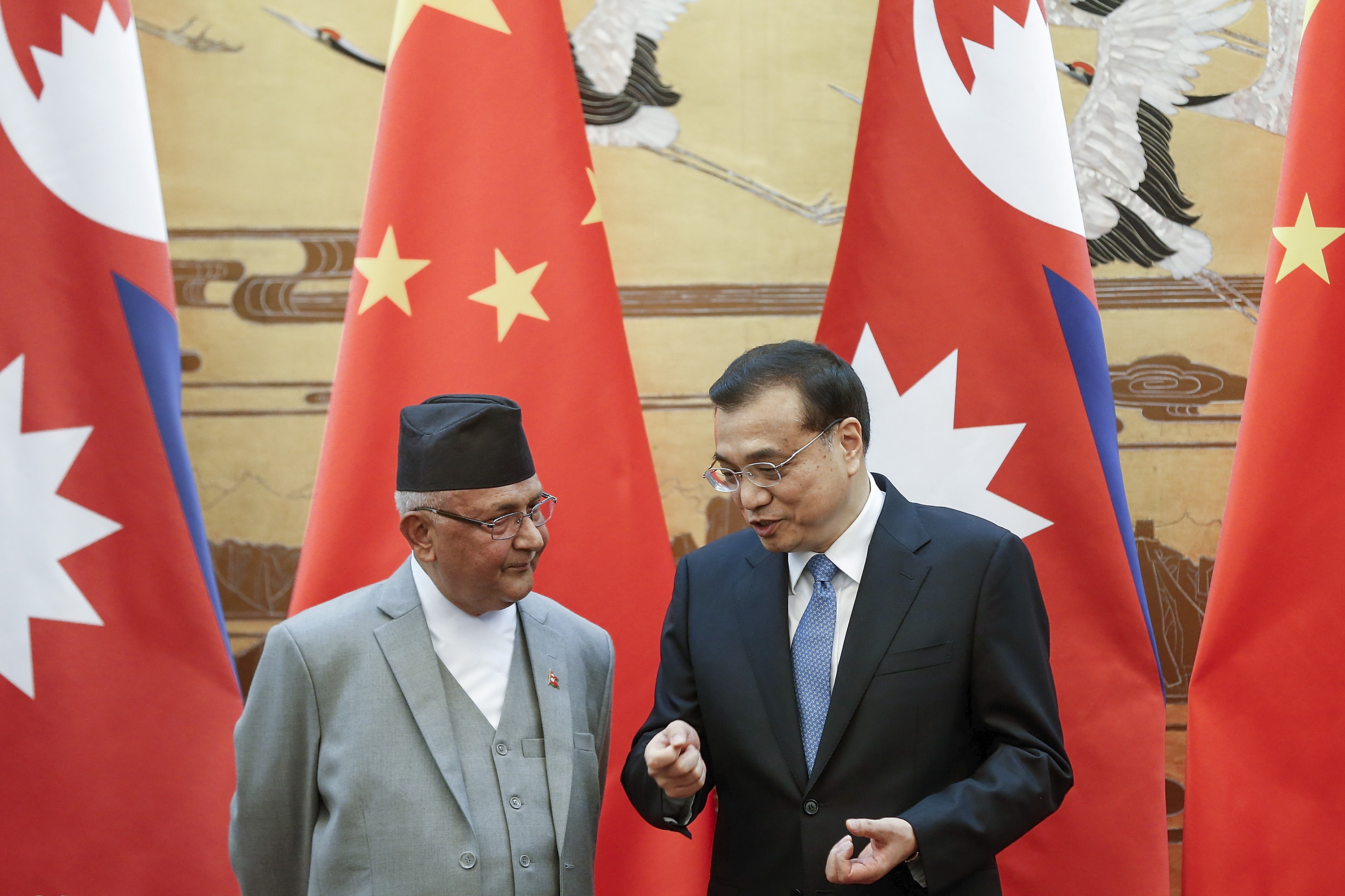 China's Premier Li Keqiang, right, talks to Nepal's Prime Minister K.P. Sharma Oli during a signing ceremony at the Great Hall of the People in Beijing on March 21, 2016