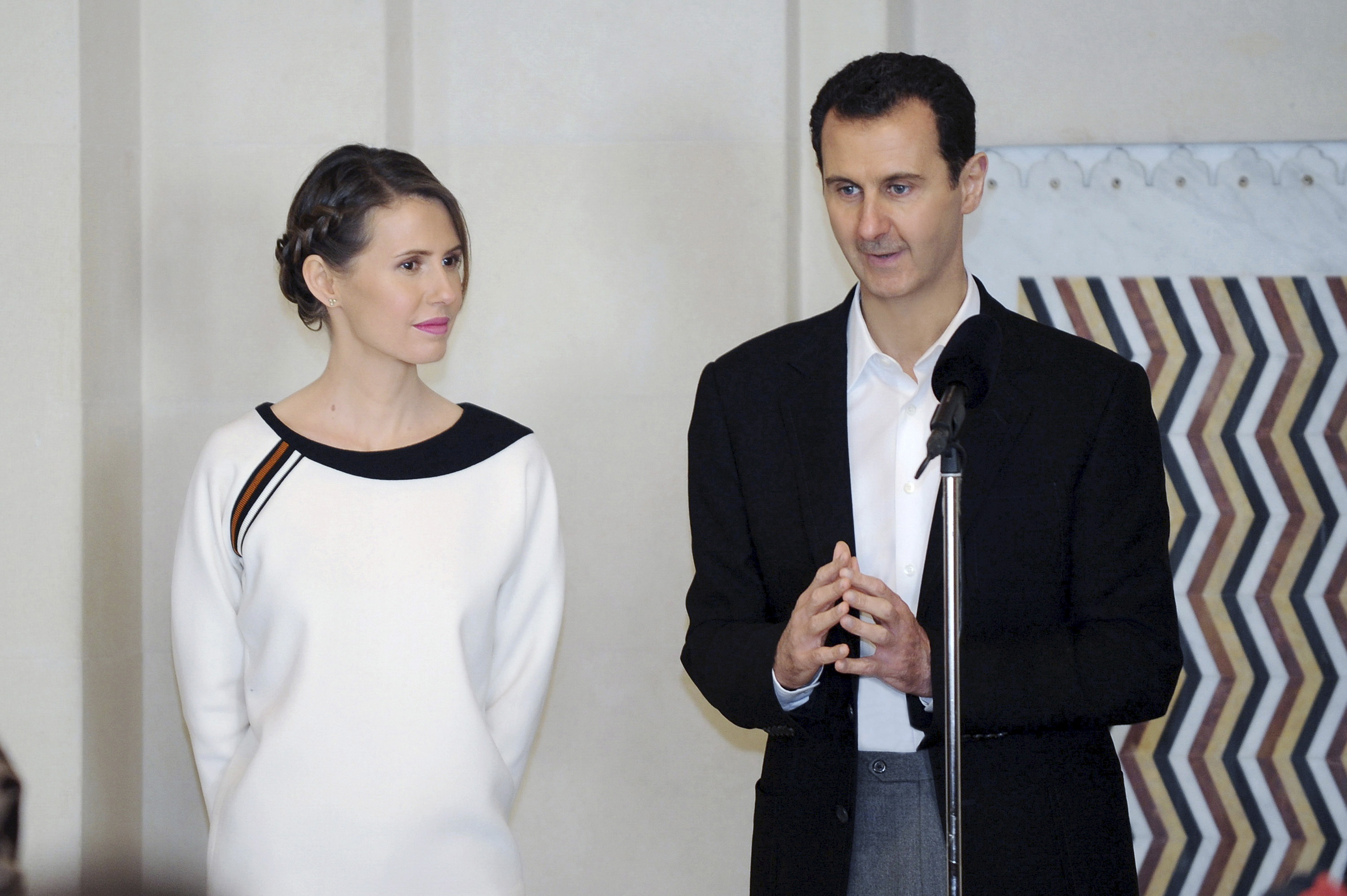 Syria's President Bashar Assad stands next to his wife Asma as he addresses injured soldiers and their mothers during a celebration marking Syrian Mother's Day in Damascus, in this handout picture provided by SANA on March 21, 2016