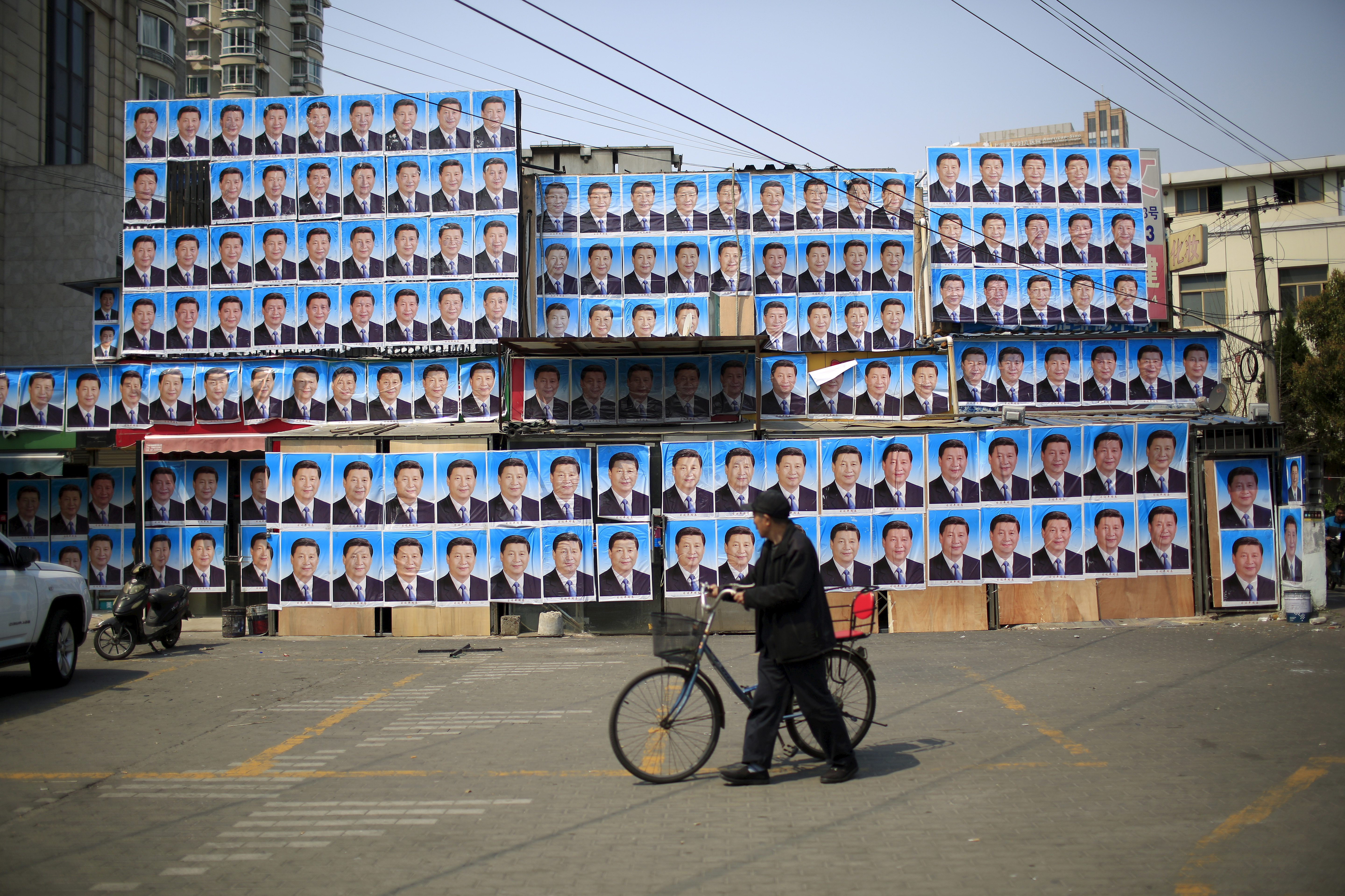 A man with a bicycle walks past a building covered in hundreds of posters of Chinese President Xi Jinping in Shanghai on March 26, 2016
