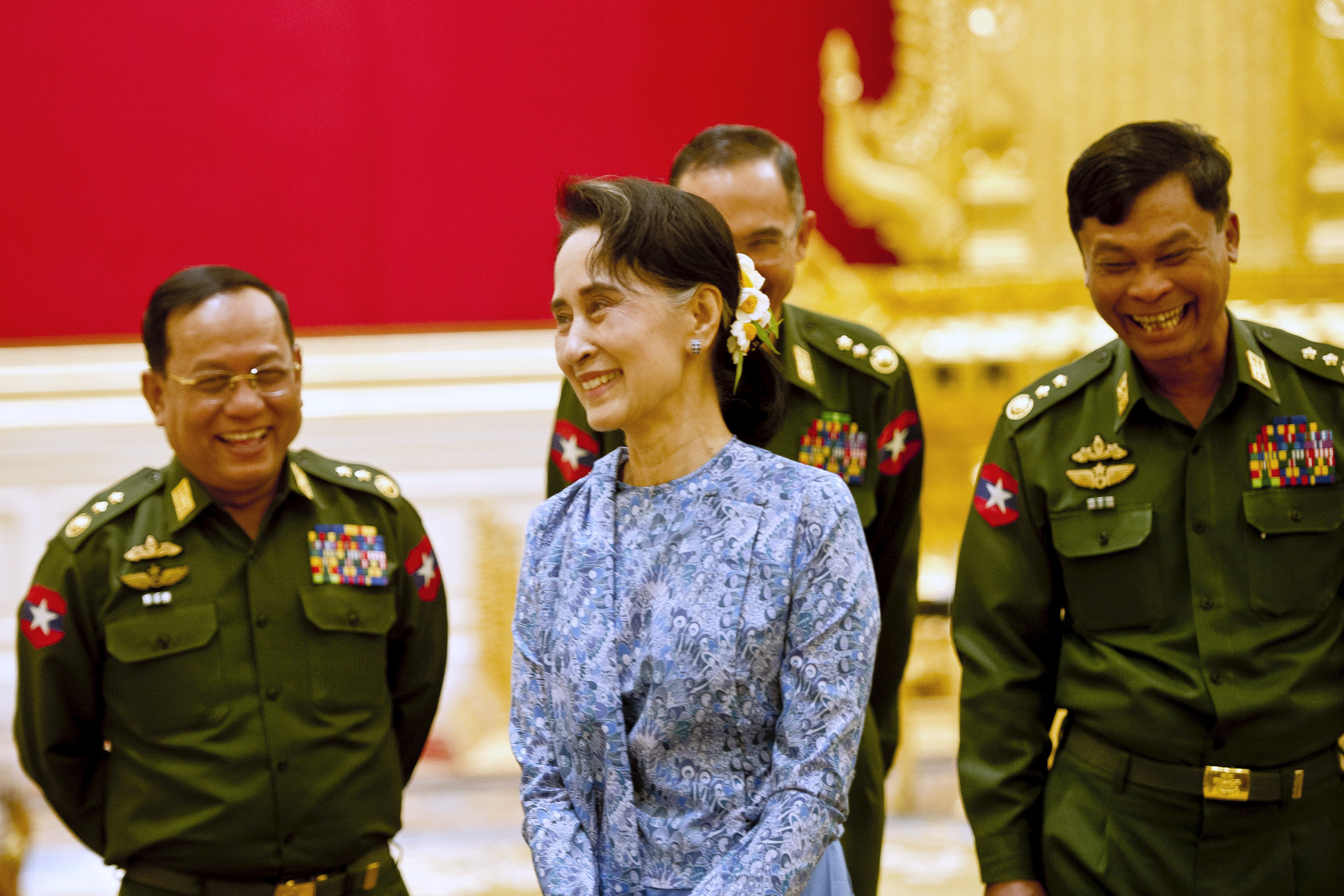 Aung San Suu Kyi, the National League for Democracy party's leader, smiles with army members during the handover ceremony at the presidential palace in Naypyitaw, Burma, on March 30, 2016