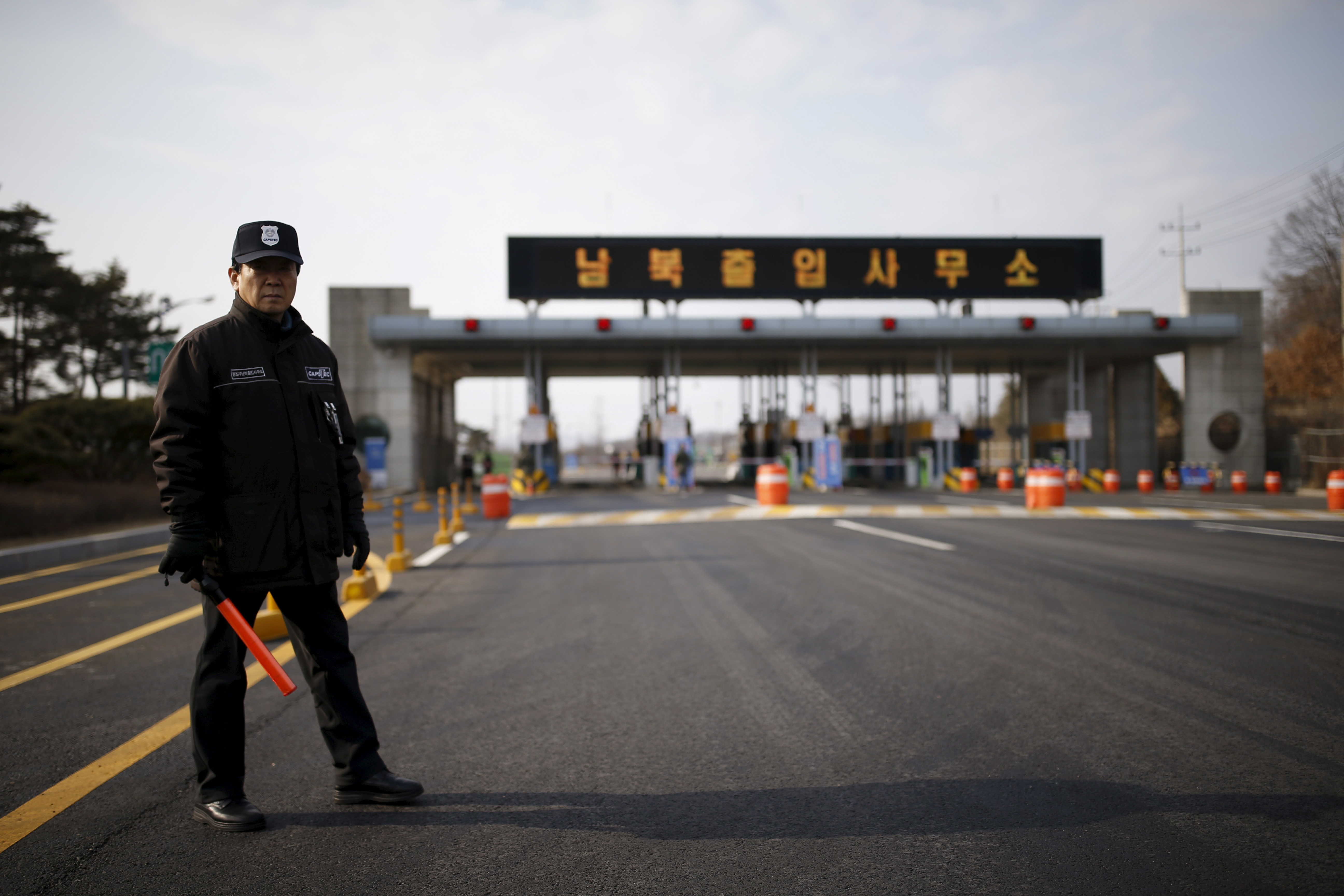 A South Korean security guard stands guard on an empty road that leads to the Kaesong Industrial Complex at the South's Customs, Immigration and Quarantine, just south of the demilitarized zone separating the two Koreas, in Paju, South Korea, on Feb. 11, 2016