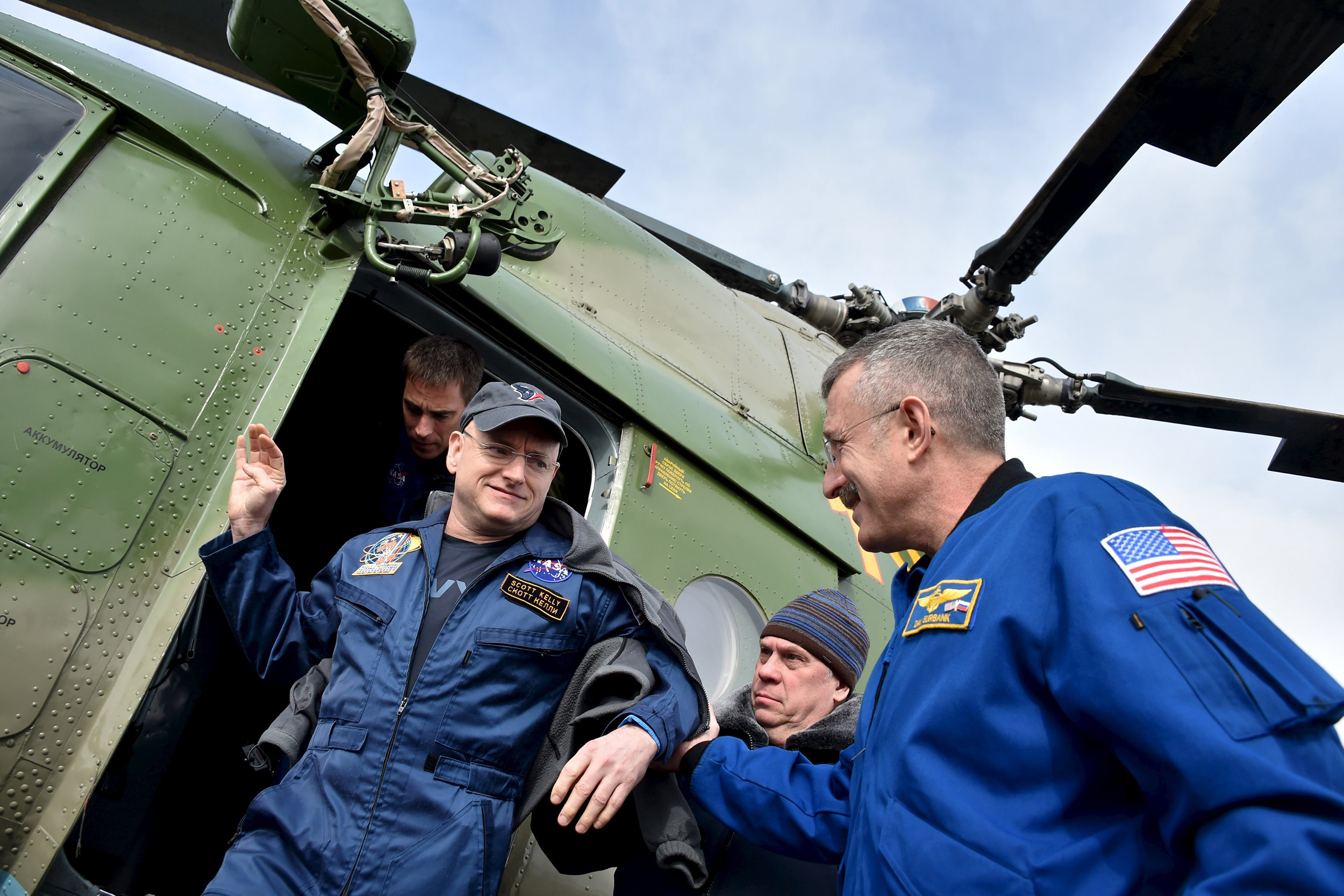 Members of NASA support team help Scott Kelly get off a helicopter at an airport in Zhezkazgan, Kazakhstan on March 2, 2016.