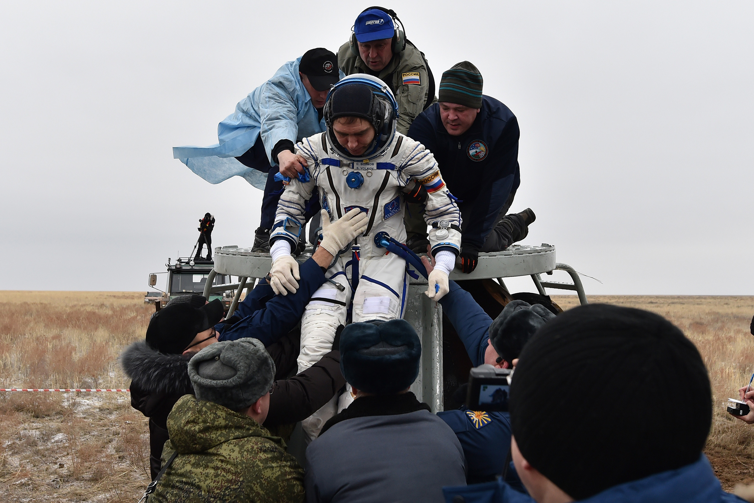 Ground personnel help International Space Station crew member Sergey Volkov of Russia get out of the Soyuz TMA-18M space capsule after landing in Kazakhstan, on March 2, 2016.