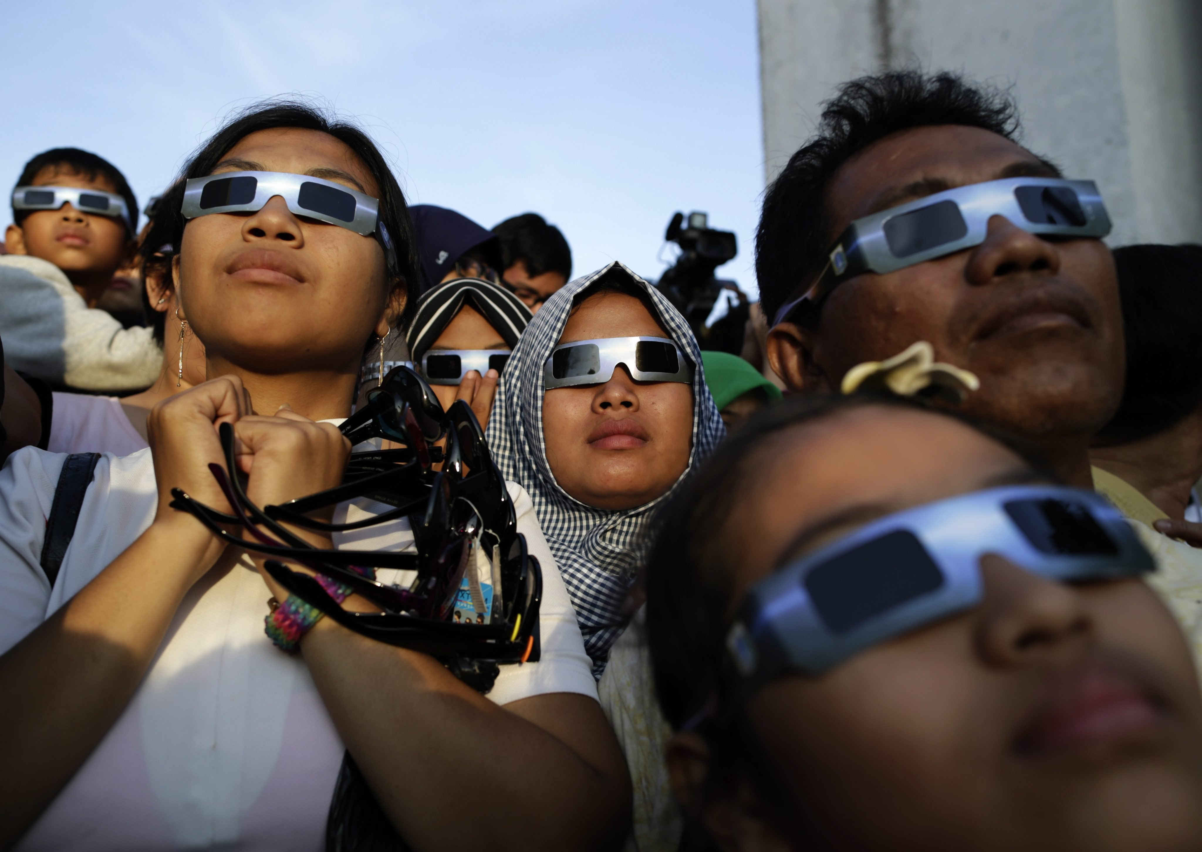 Indonesian residents wear eclipse glasses to watch a solar eclipse outside a planetarium in Jakarta, on March 9.