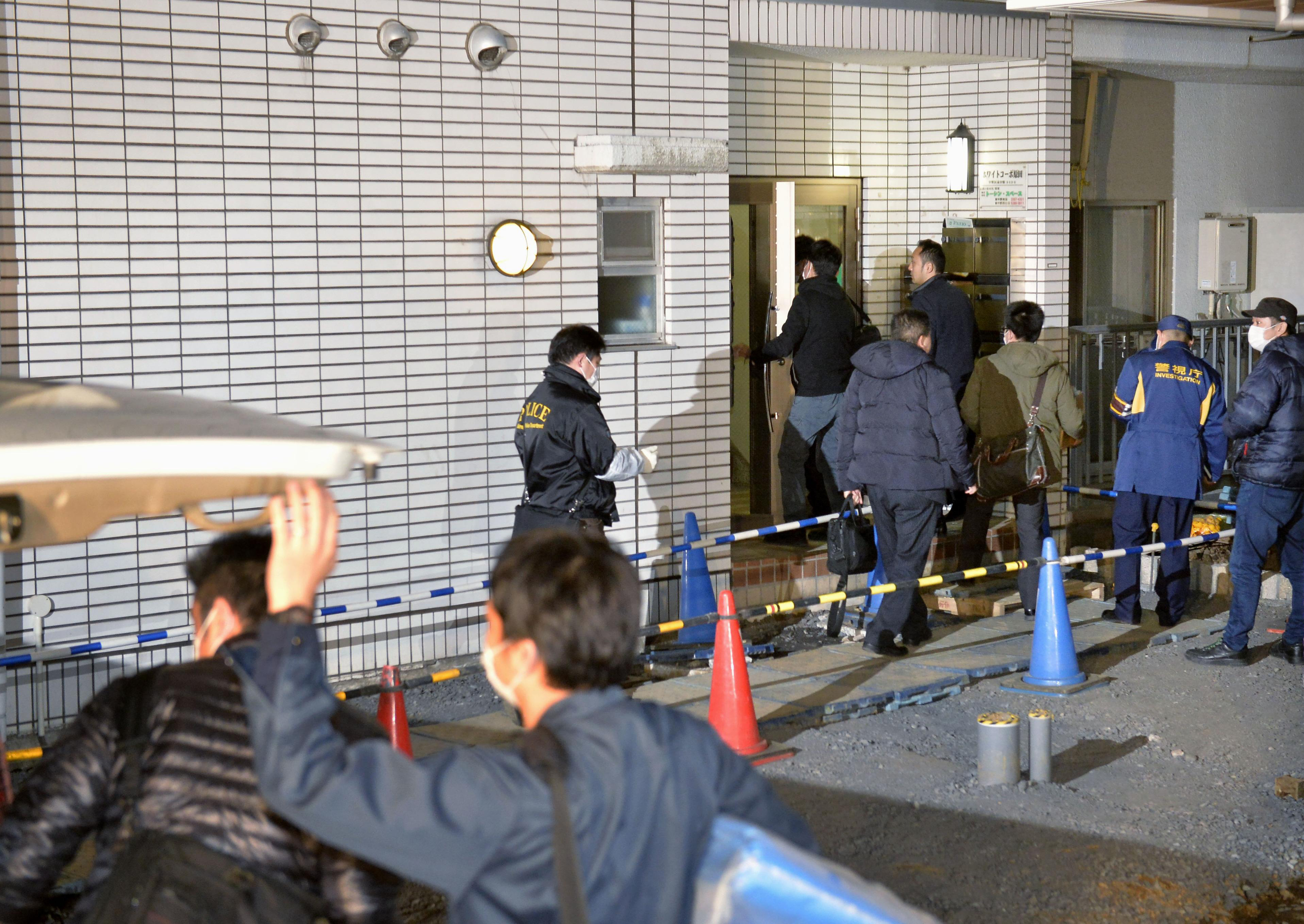 Police officers arrive for investigation of the apartment of abduction suspect Kabu Terauchi in Tokyo on March 28, 2016.