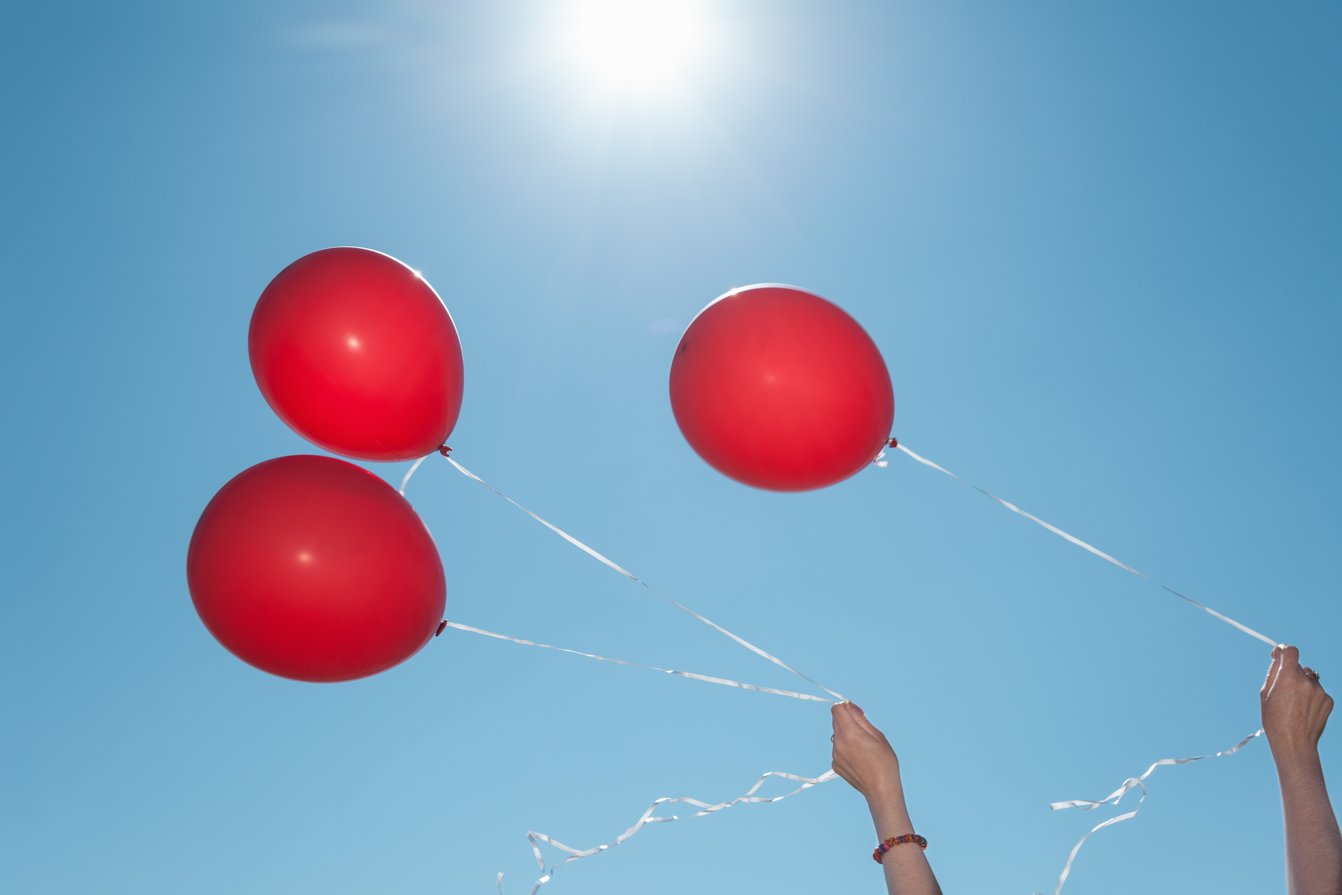 Hands holding three red balloons against blue sky