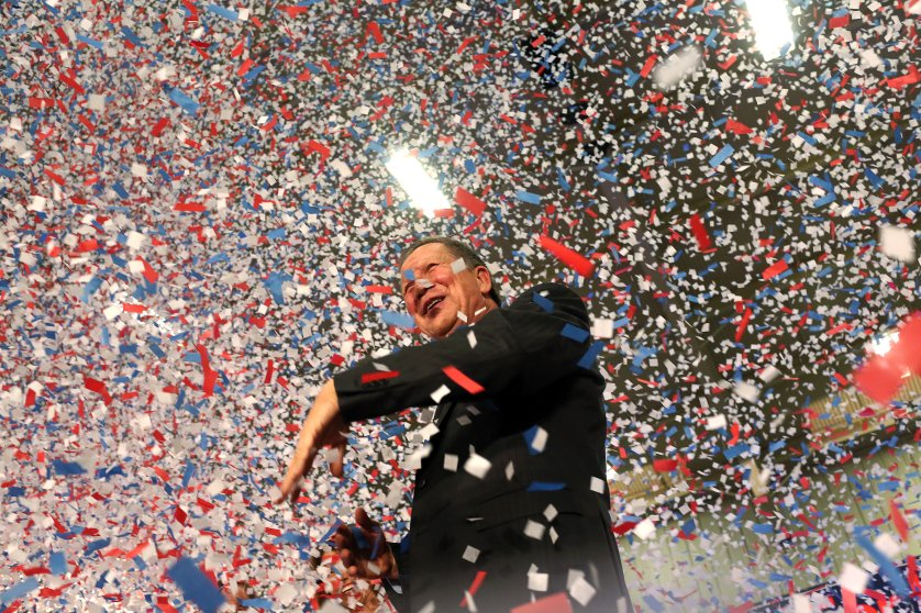 Republican presidential candidate, Ohio Gov. John Kasich waves confetti out of his way after giving his victory speech at Baldwin-Wallace University in Berea, Ohio on March 15, 2016.