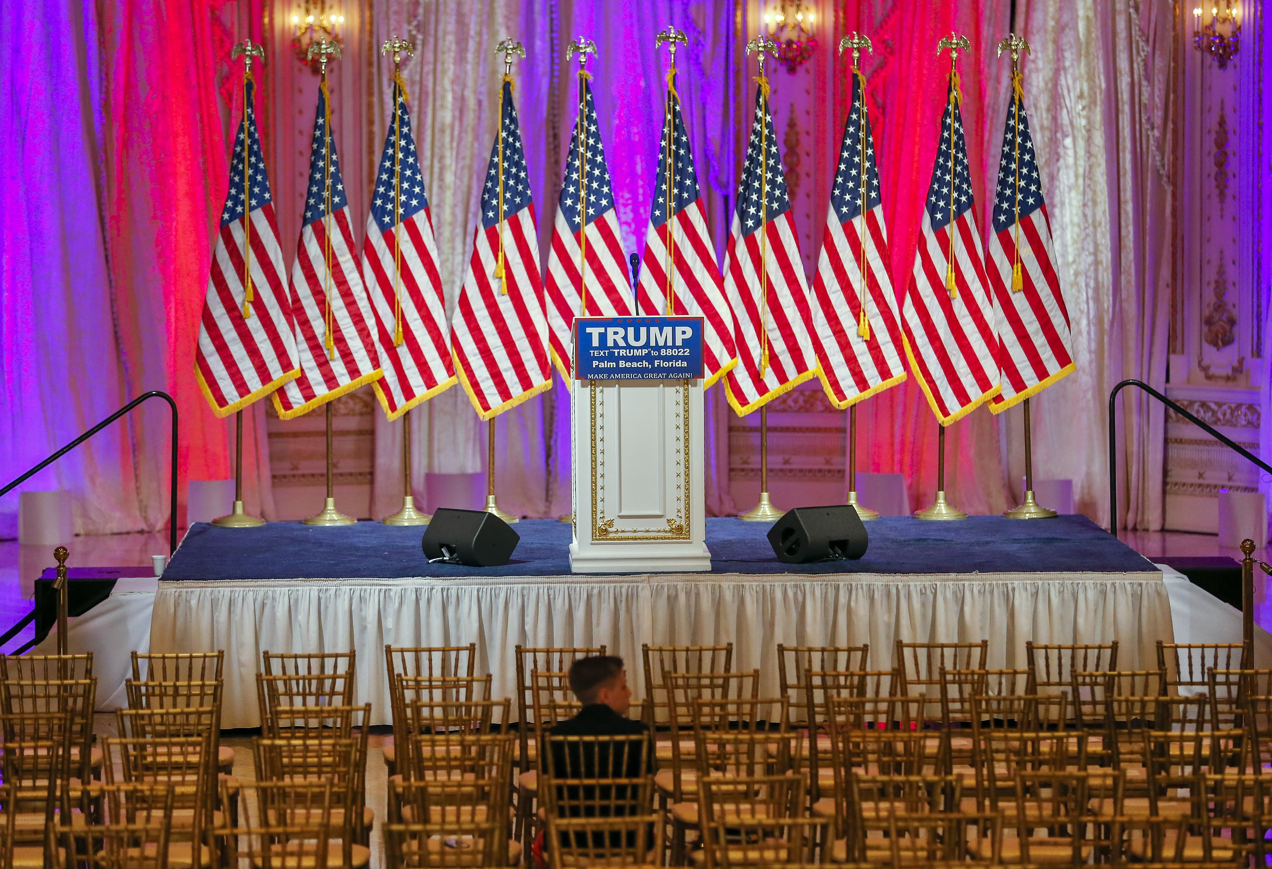 A boy sits near the stage where Republican presidential candidate Donald Trump is scheduled to participate in a news conference inside a ballroom at the Mar-a-Lago Club in Palm Beach, Fla. on March 15, 2016.