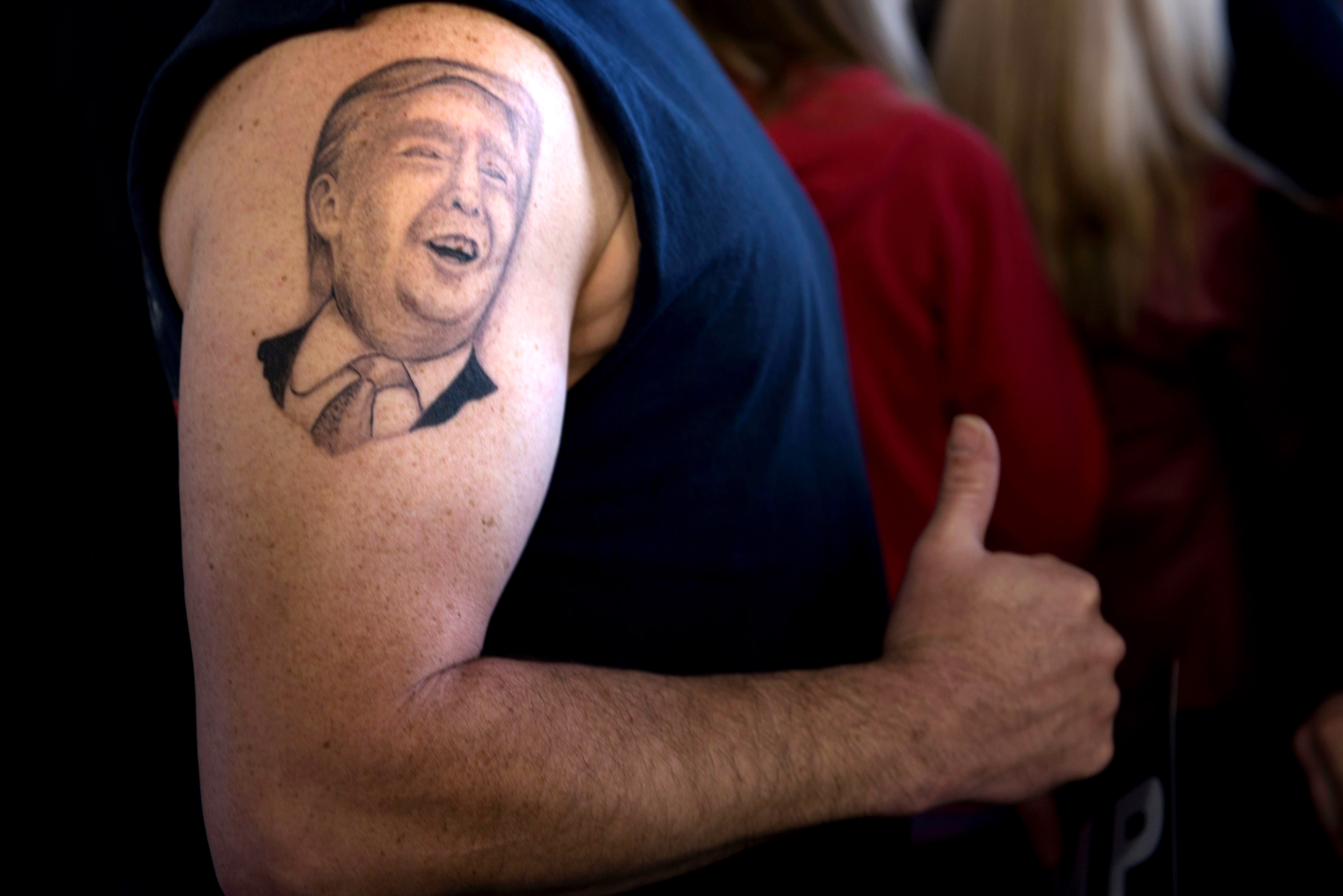 Anthony Borbell shows off his tattoo, a likeness of Donald Trump, during a rally on March 14 in Vienna Center, Ohio.