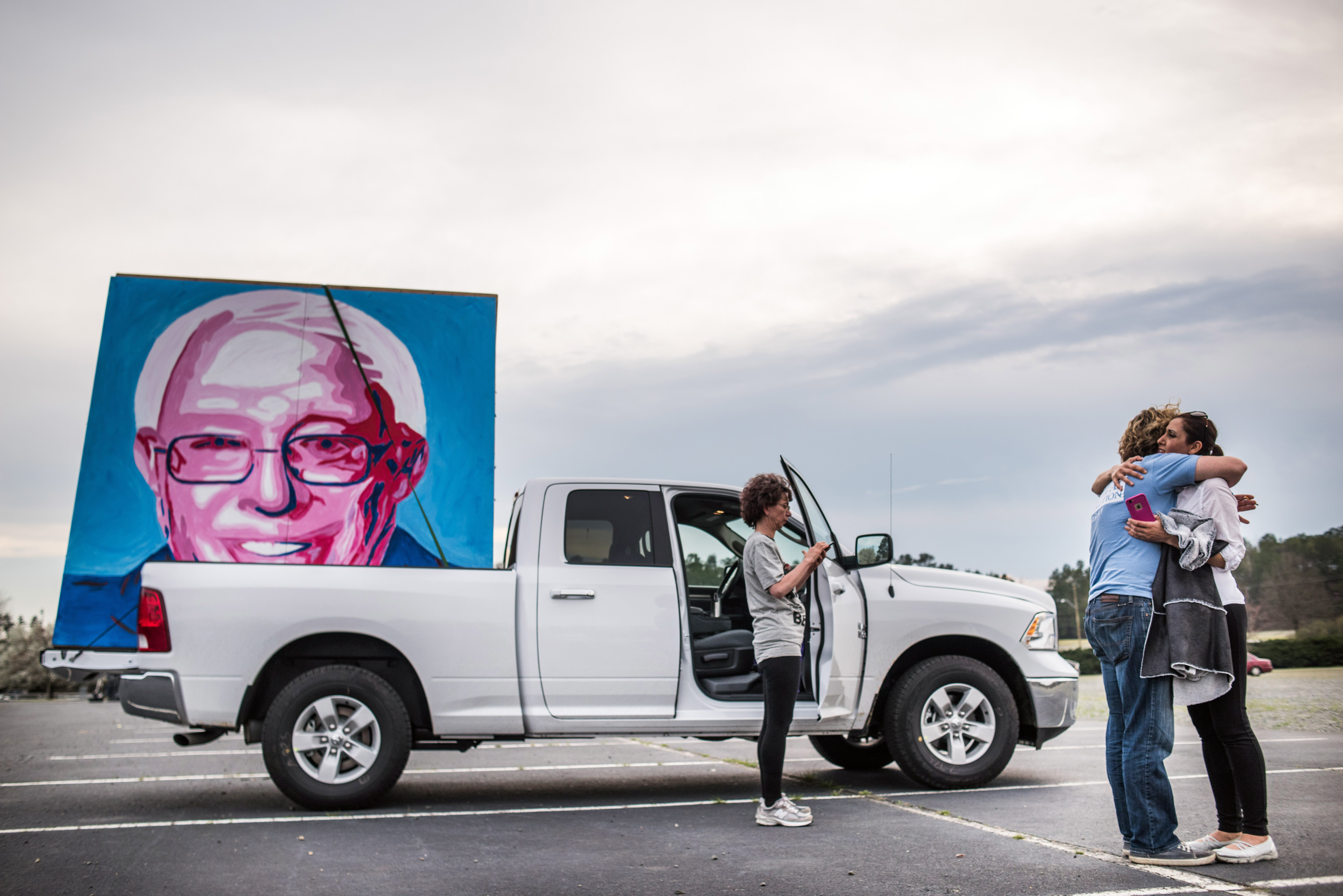 Joseph Kelly, left, hugs Farzaneh Rezaei after loading his large painting showing the likeness of  Bernie Sanders into a truck following a campaign rally on March 14 in Charlotte, N.C.