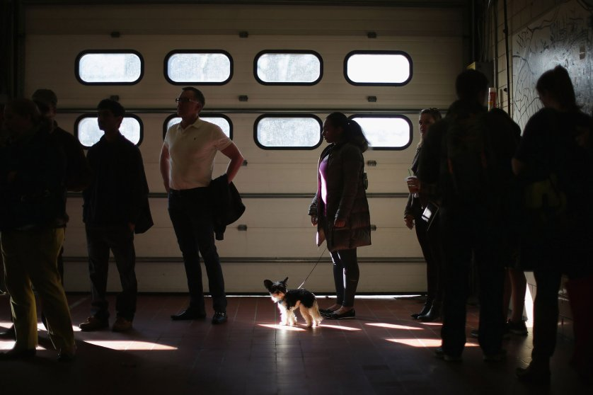 Nina Ward and her dog Leo wait in line with other voters at Arlington County Fire Station 10 during Super Tuesday votingin Arlington, Va.