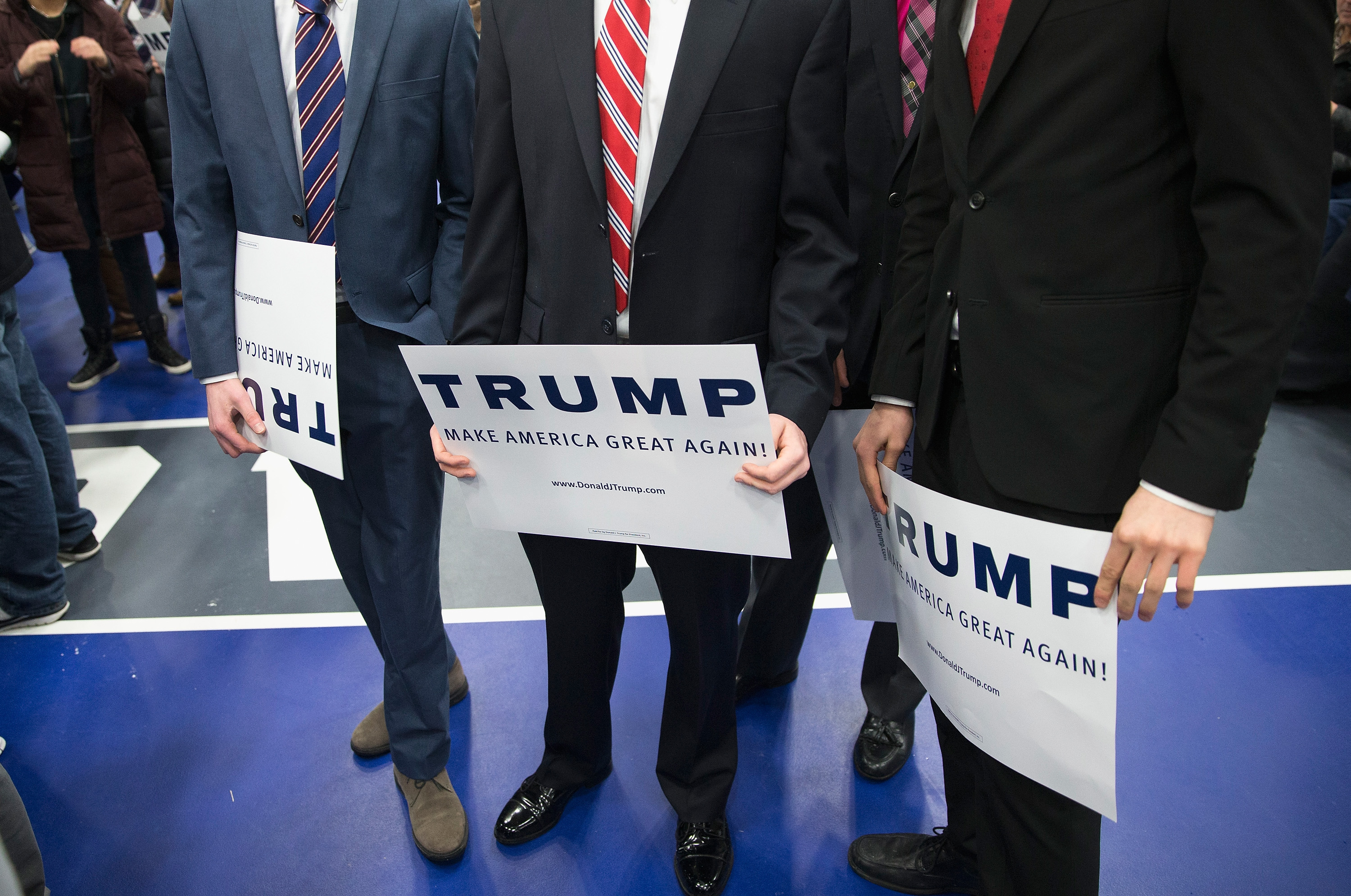 Men hold signs while waiting for Republican presidential candidate Donald Trump to arrive for a rally at Macomb Community College in Warren, Mich., on March 4, 2016.