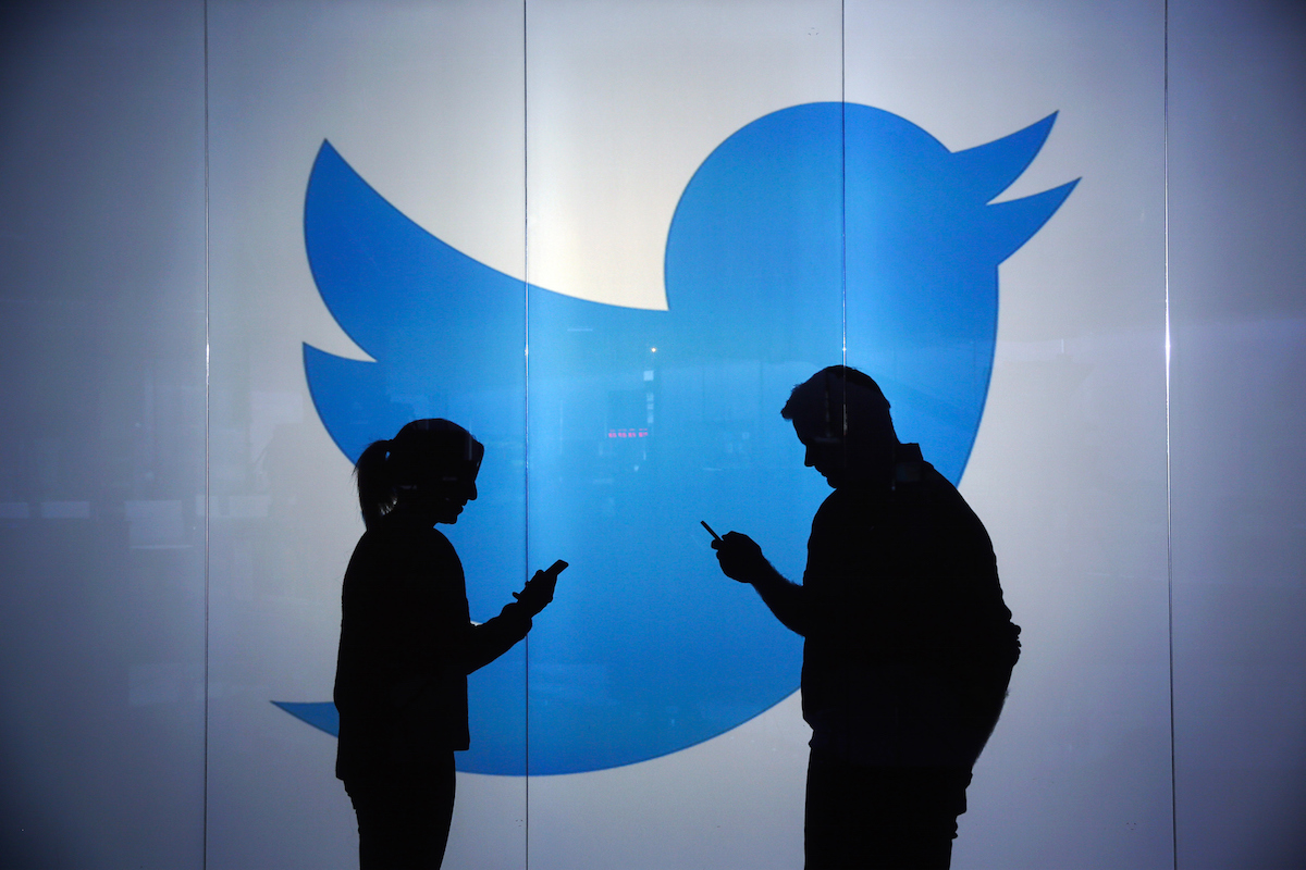 People check mobile devices whilst standing against an illuminated wall bearing Twitter Inc.'s logo in this arranged photograph in London on Jan. 5, 2016.
