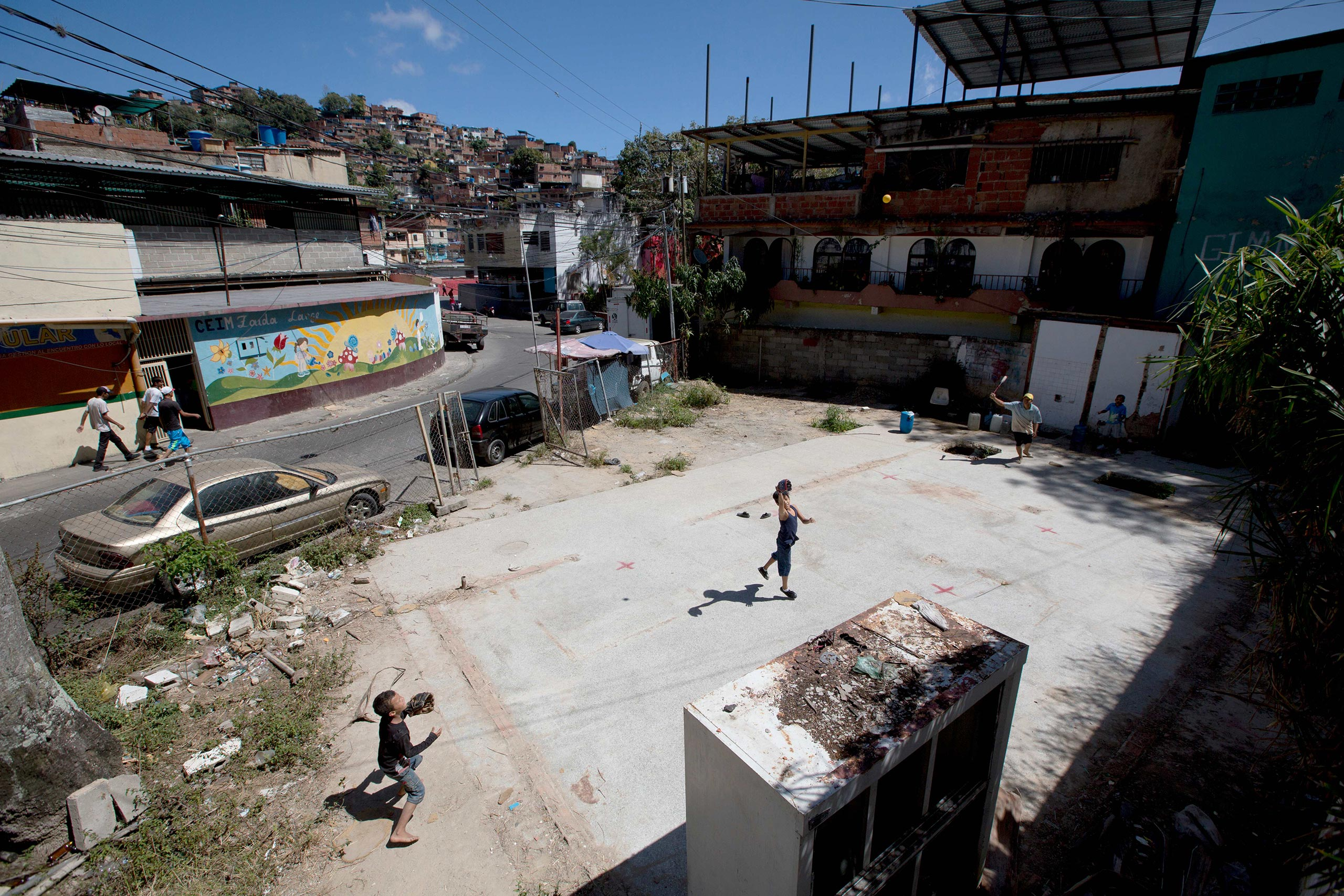 A man and his sons play baseball as they collect drinking water from an abandoned social center in the La Dolorita neighborhood of Caracas, Venezuela, Feb. 10, 2016. Officials say the water shortage is due to a severe drought caused by the El Nino.