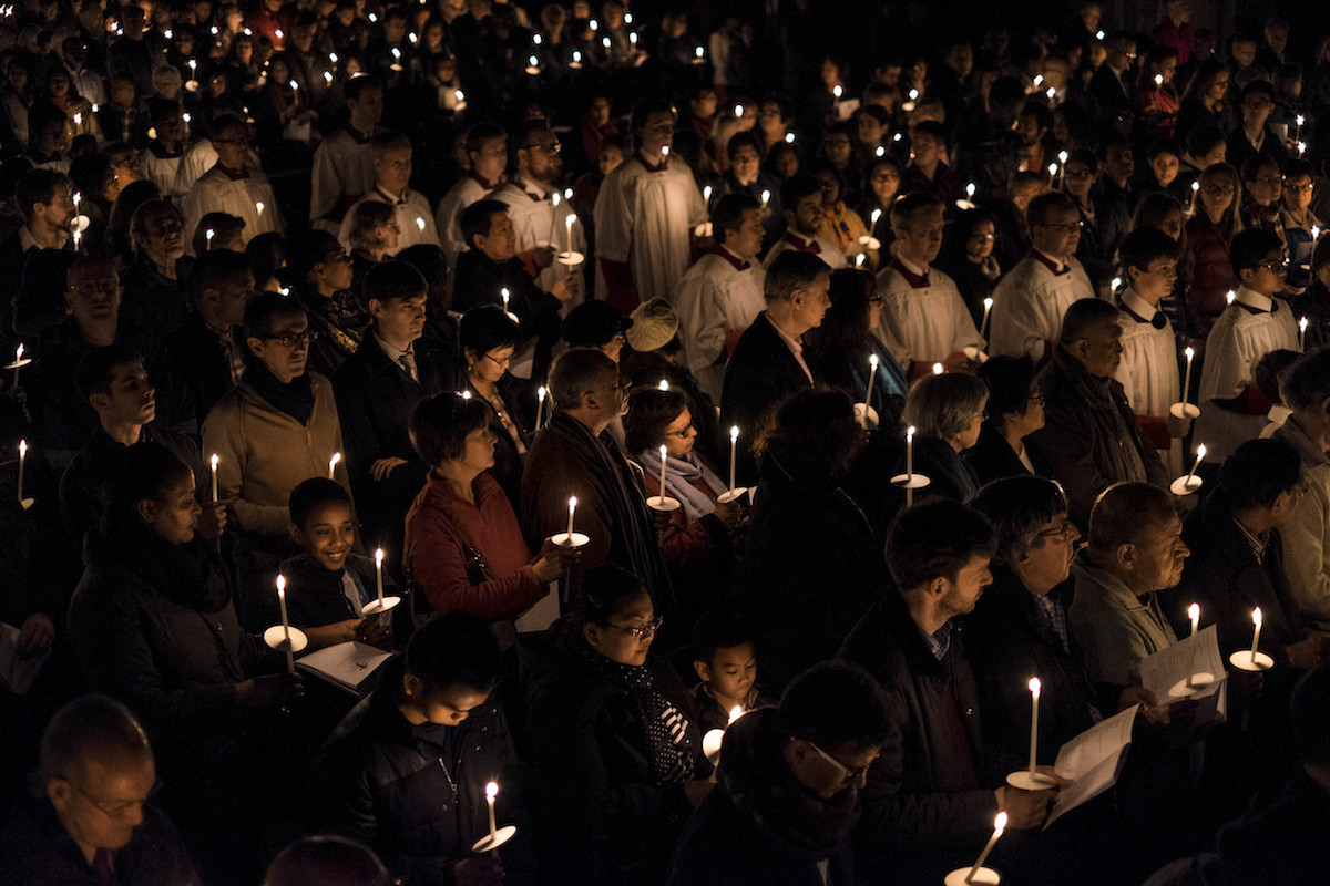 People hold candles during The Easter Vigil service on the evening of Holy Saturday at Westminster Cathedral on April 4, 2015 in London