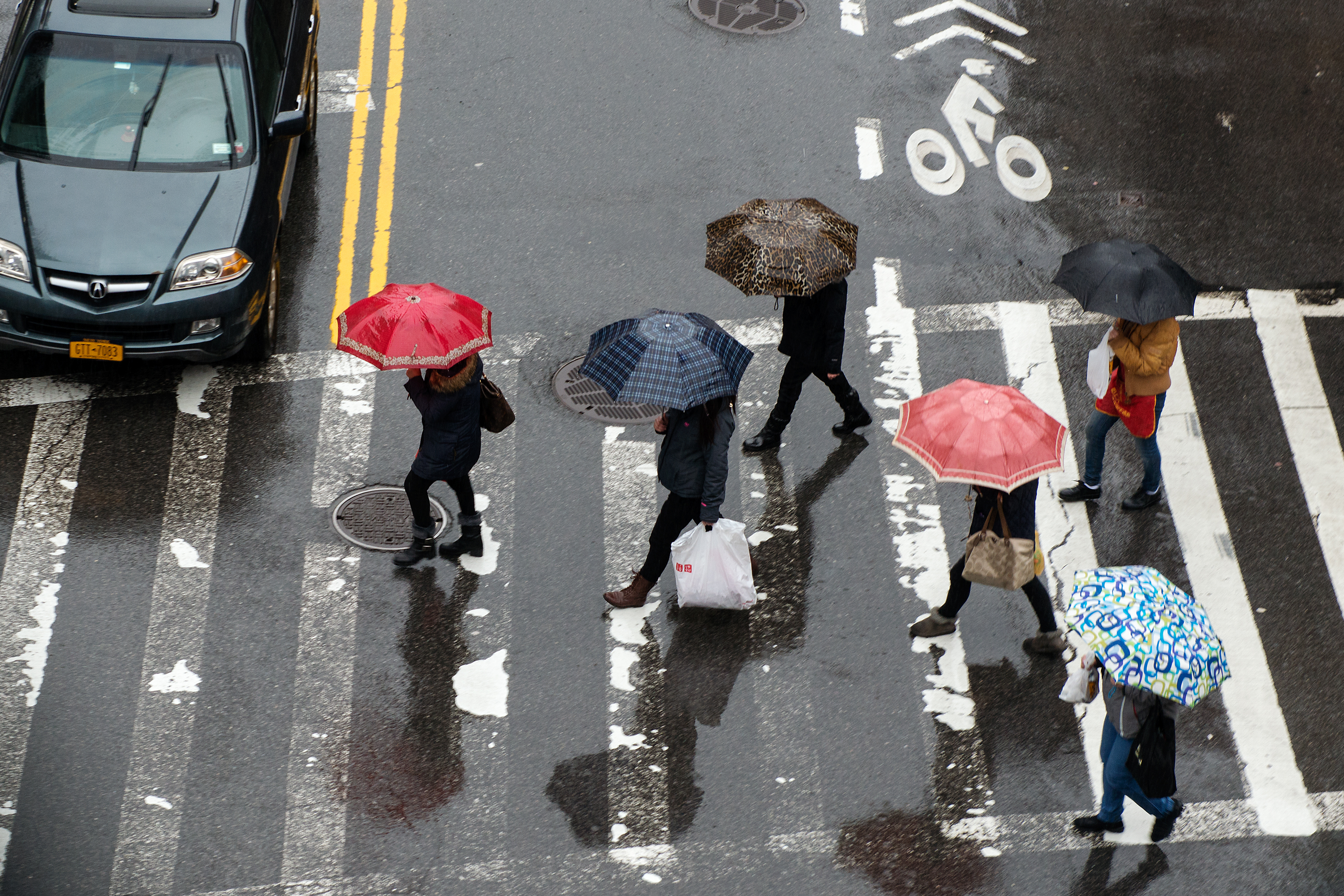 NEW YORK, NY - FEBRUARY 24: Pedestrians cross the street in Chinatown on February 24, 2016 in New York City.  According to the National Weather Service, as much as 1.5 inches of rain was expected throughout the day and a wind advisory was to begin at 6 pm. (Photo by Bryan Thomas/Getty Images)