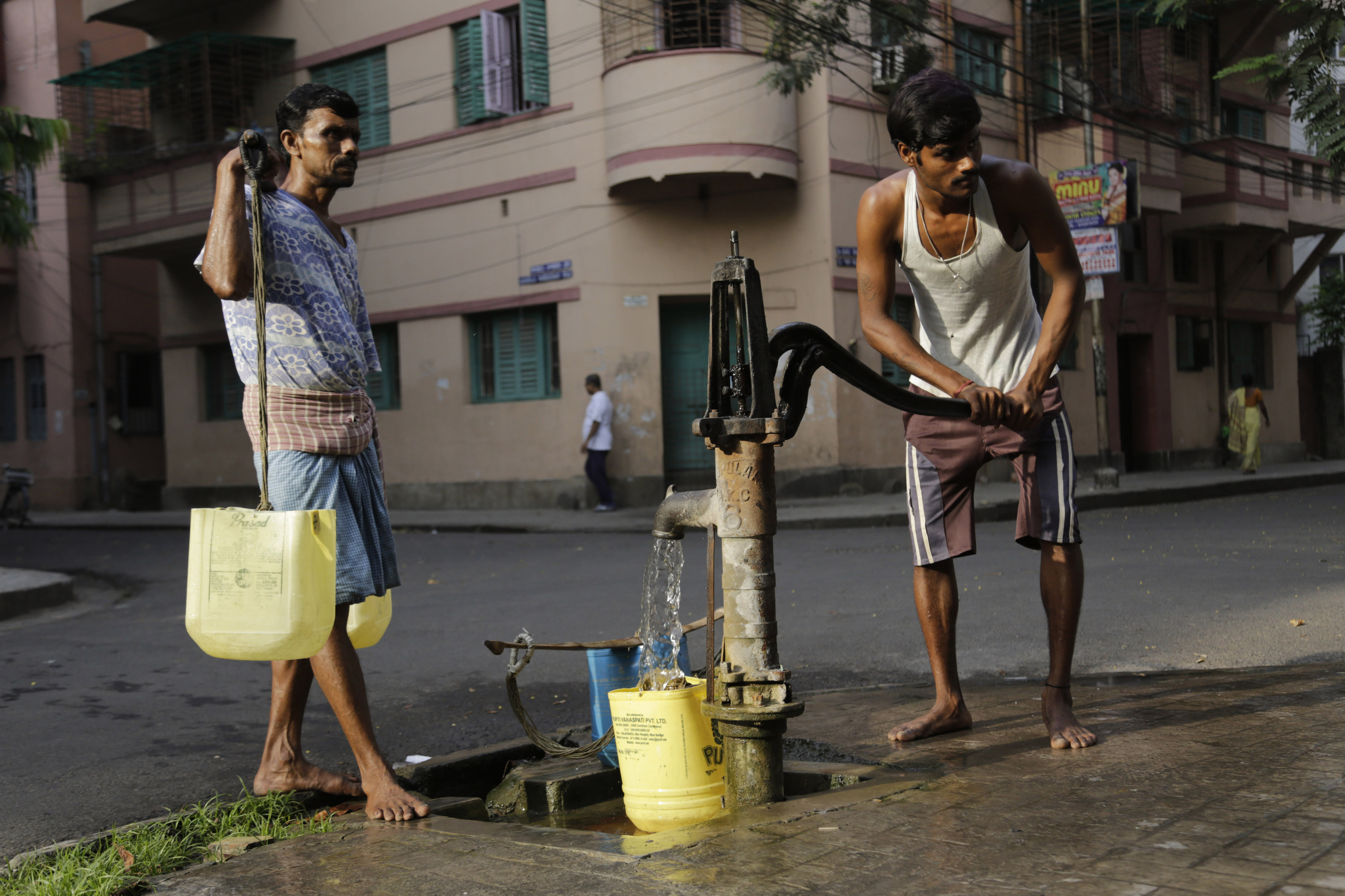 A water man fills drinking water from a roadside hand pump while another waits to deliver in houses in Kolkata, India, March 22, 2016.