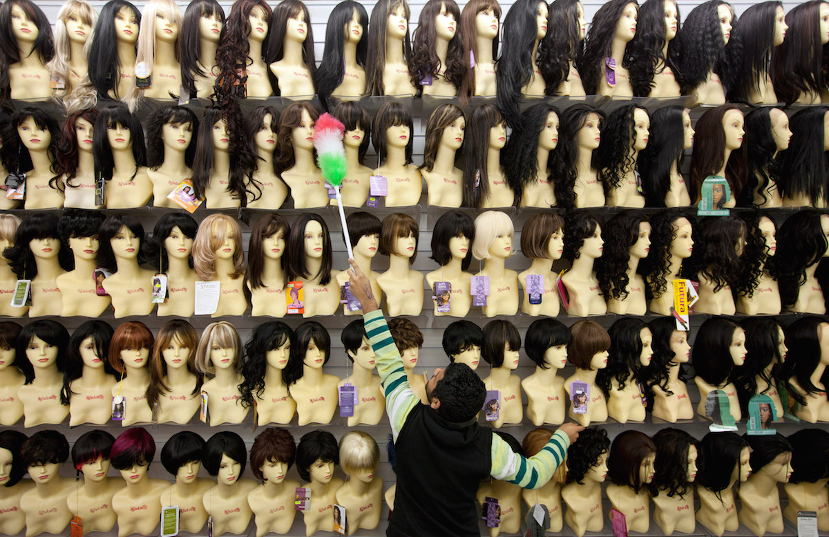 A man dusts shop mannequins displaying wigs in a hair and beauty store in Brixton on Feb. 2, 2012 in London