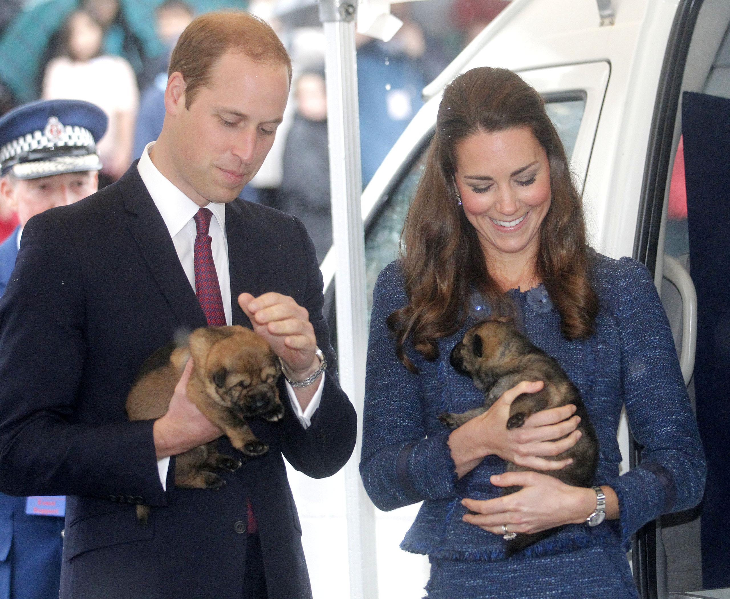 Prince William, Duke of Cambridge and Catherine, Duchess of Cambridge hold puppies during a visit to the Royal New Zealand Police College in Wellington, New Zealand on April 16, 2014.