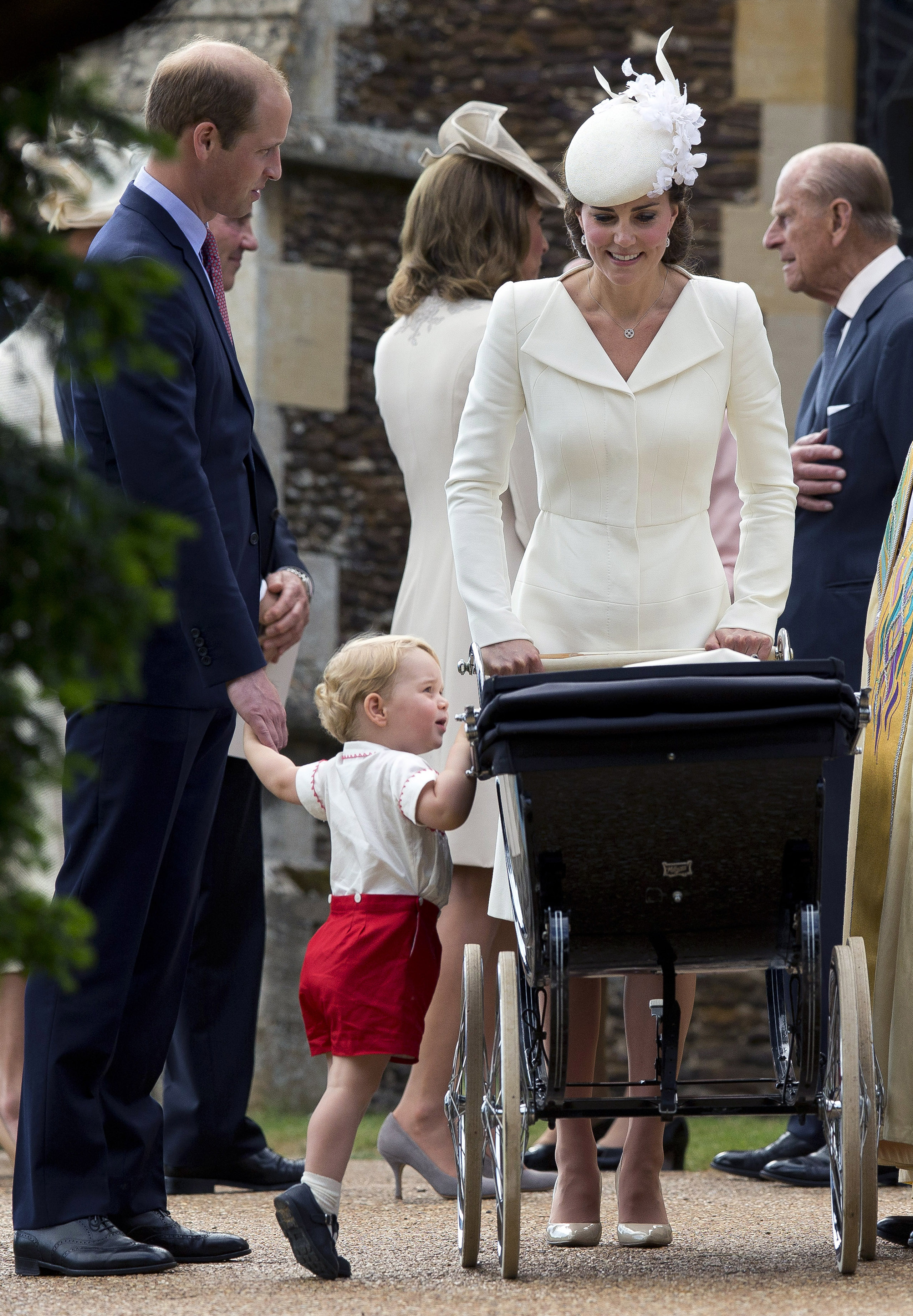 Catherine, Duchess of Cambridge, Prince William, Duke of Cambridge, Princess Charlotte of Cambridge and Prince George of Cambridge leave the Church of St Mary Magdalene on the Sandringham Estate after the Christening of Princess Charlotte of Cambridge in King's Lynn, England on July 5, 2015.
