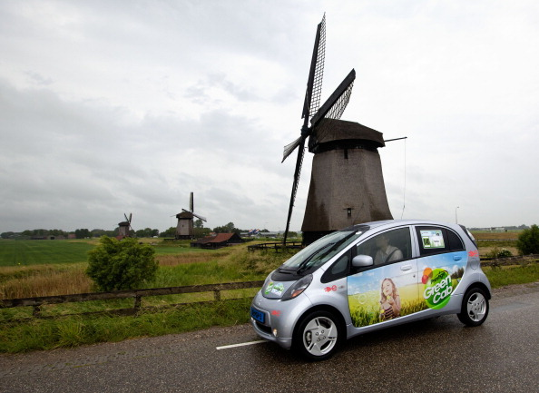 A Mitsubishi i-MiEv drives past Dutch windmills in the 2011 Electric Car Rally as part of World Environment Day activities on June 5, 2011 near Zaandam, The Netherlands.
