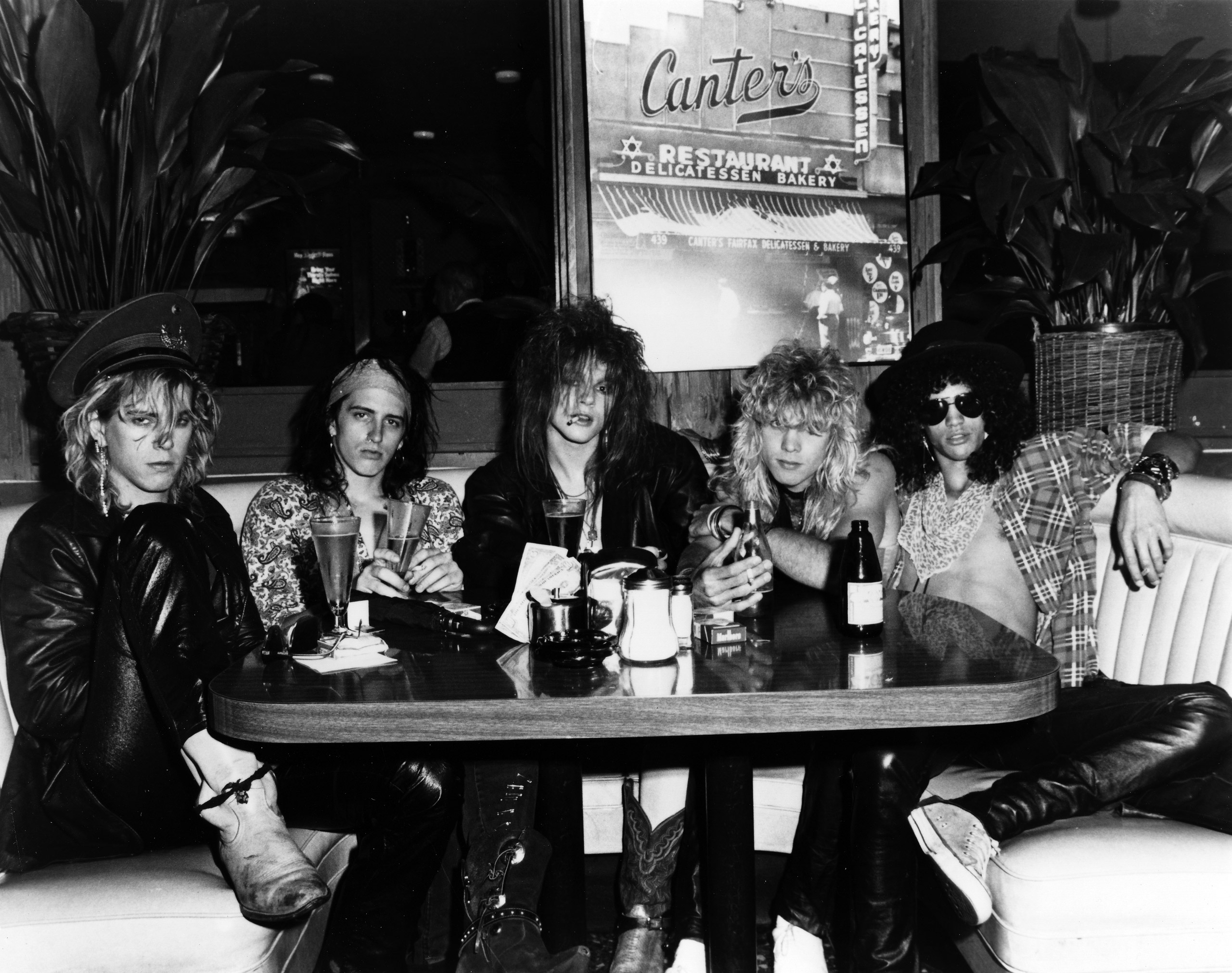 Duff McKagan, Izzy Stradlin, Axl Rose, Steven Adler and Slash of Guns n' Roses pose for a portrait in a booth at Canter's Deli adjacent to the Kibitz Room bar in June 1985 in Los Angeles.