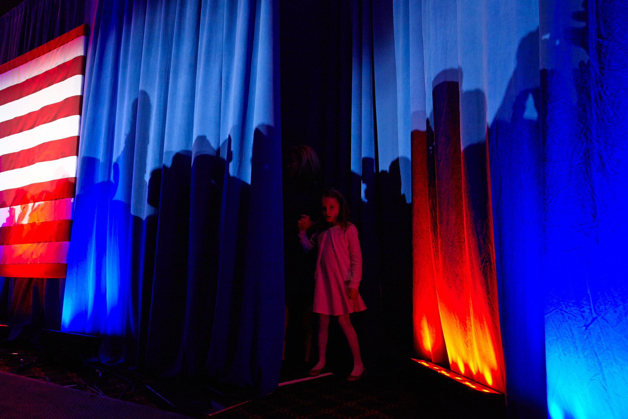 Republican presidential candidate Ted Cruz's daughter peers out from a curtain during the Texas Senator's primary night campaign event on April 5, 2016, in Milwaukee.