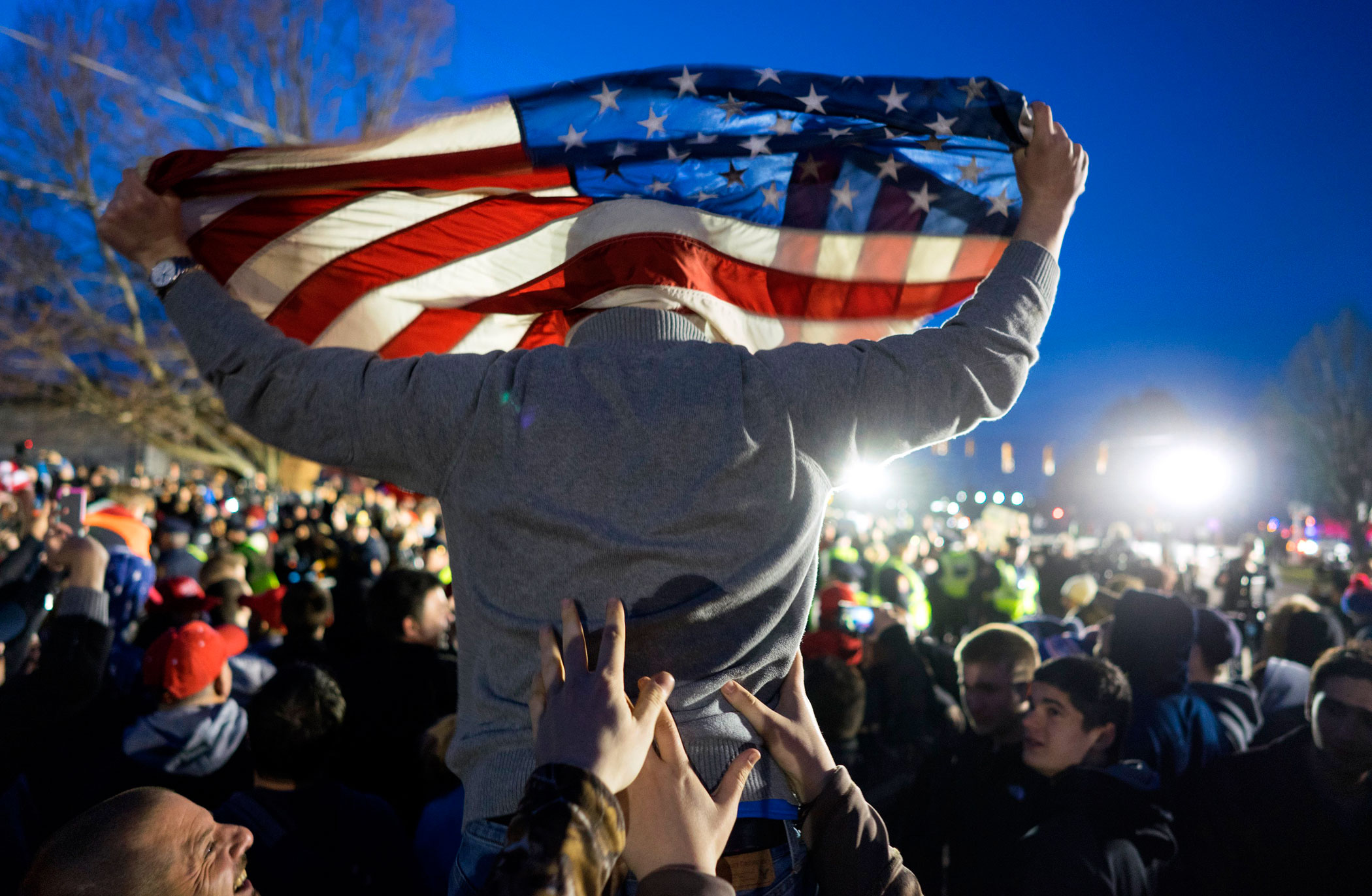 A Donald Trump supporter is hoisted up while facing protesters  near the site of a campaign appearance by the Republican presidential candidate in Bethpage, N.Y. on April 6, 2016.