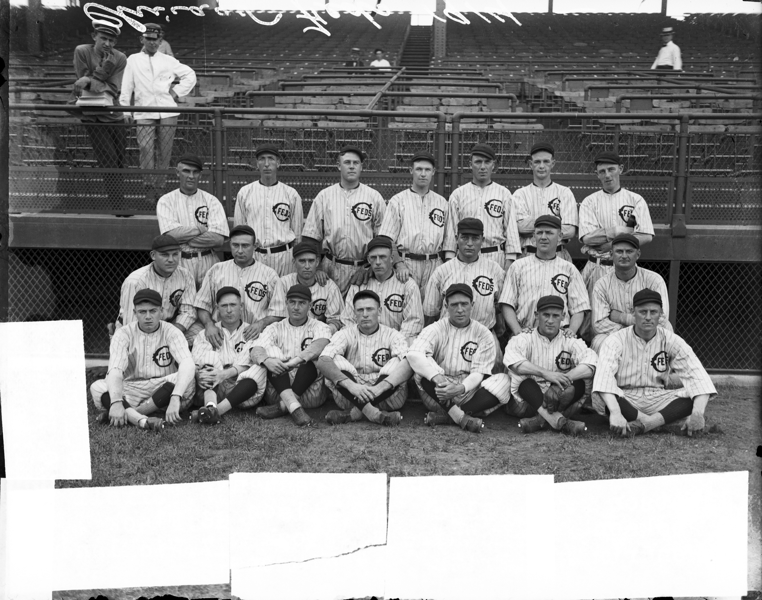 Members of the Federal League's Chicago Whales baseball team sitting and standing in front of grandstands at Weeghman Park, Chicago, 1914. Weeghman Park was renamed Wrigley Field in 1926.
