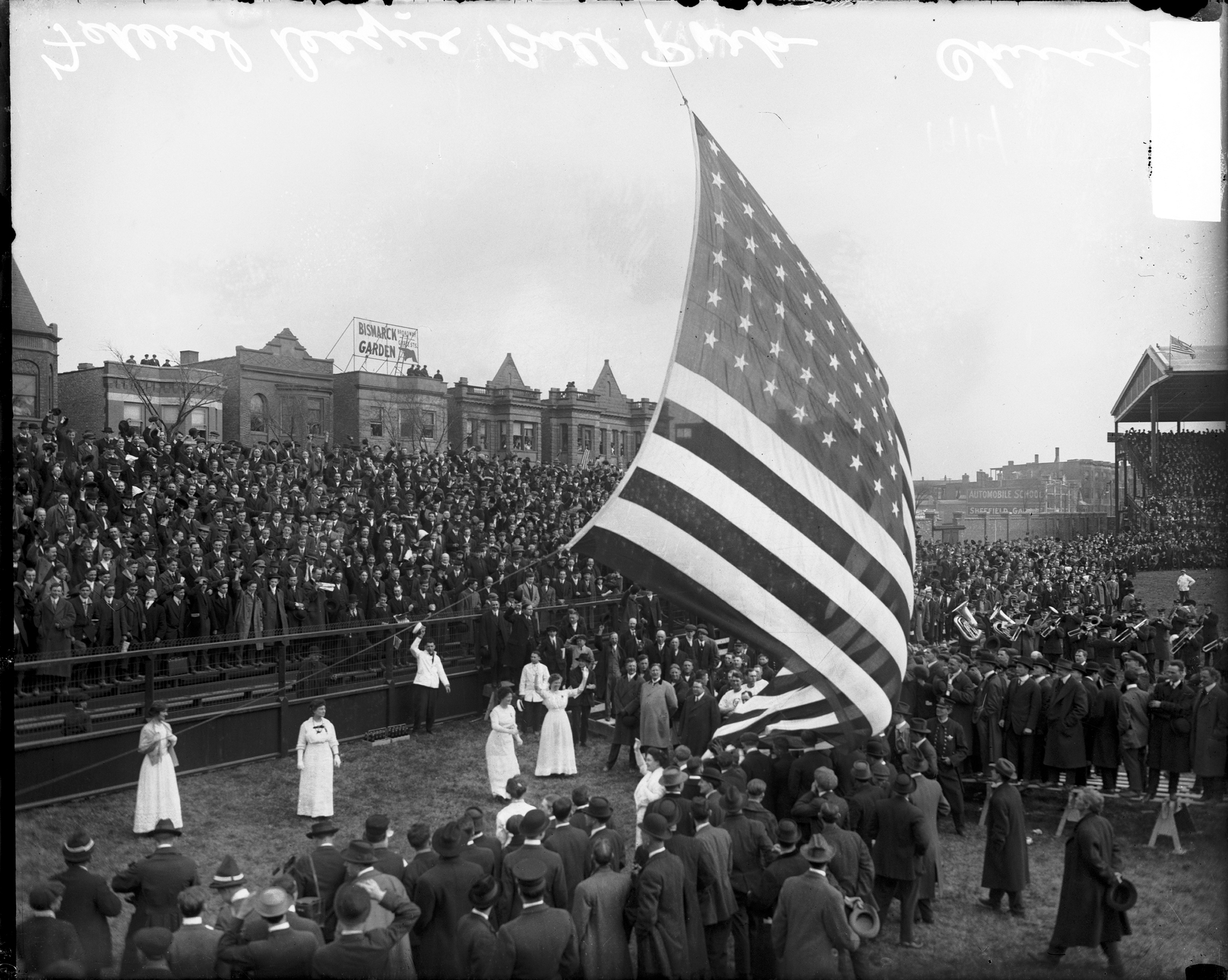 View of crowds standing on the field and in bleachers during a flag-raising ceremony at Weeghman Park, Chicago, 1914.