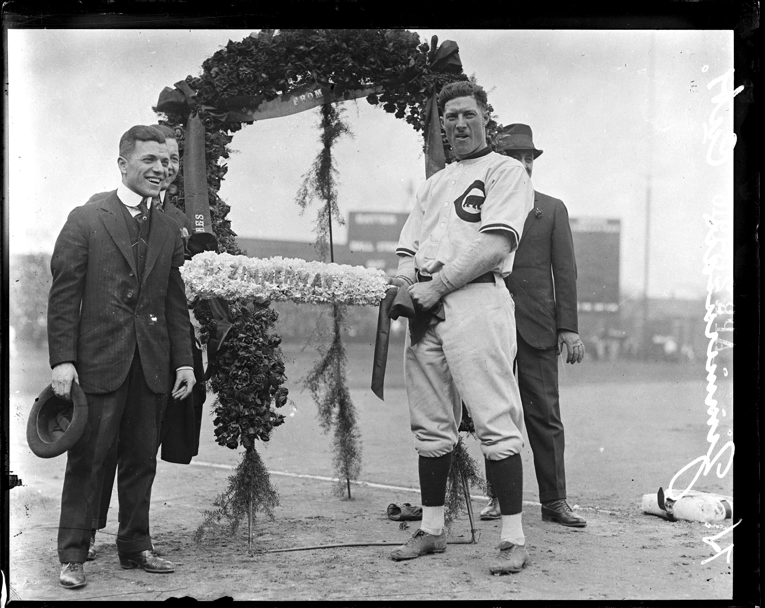 National League's Chicago Cubs baseball player Heinie Zimmerman standing in front of a floral arch at Weeghman Park, Chicago, 1916.