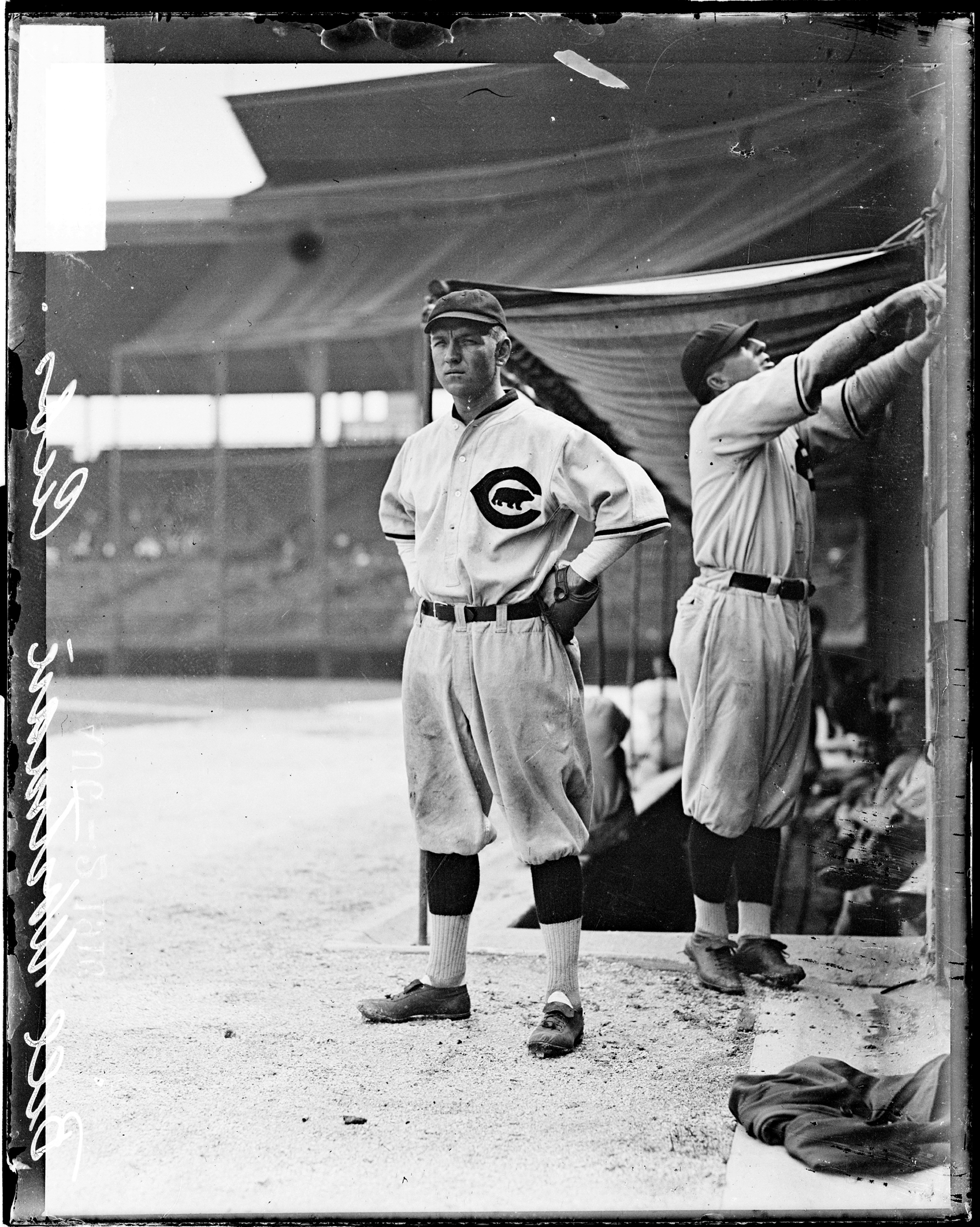 National League's Chicago Cubs baseball player Bill Wortman and an unidentified teammate standing outside the dugout on the field at Weeghman Park, Chicago, 1916.