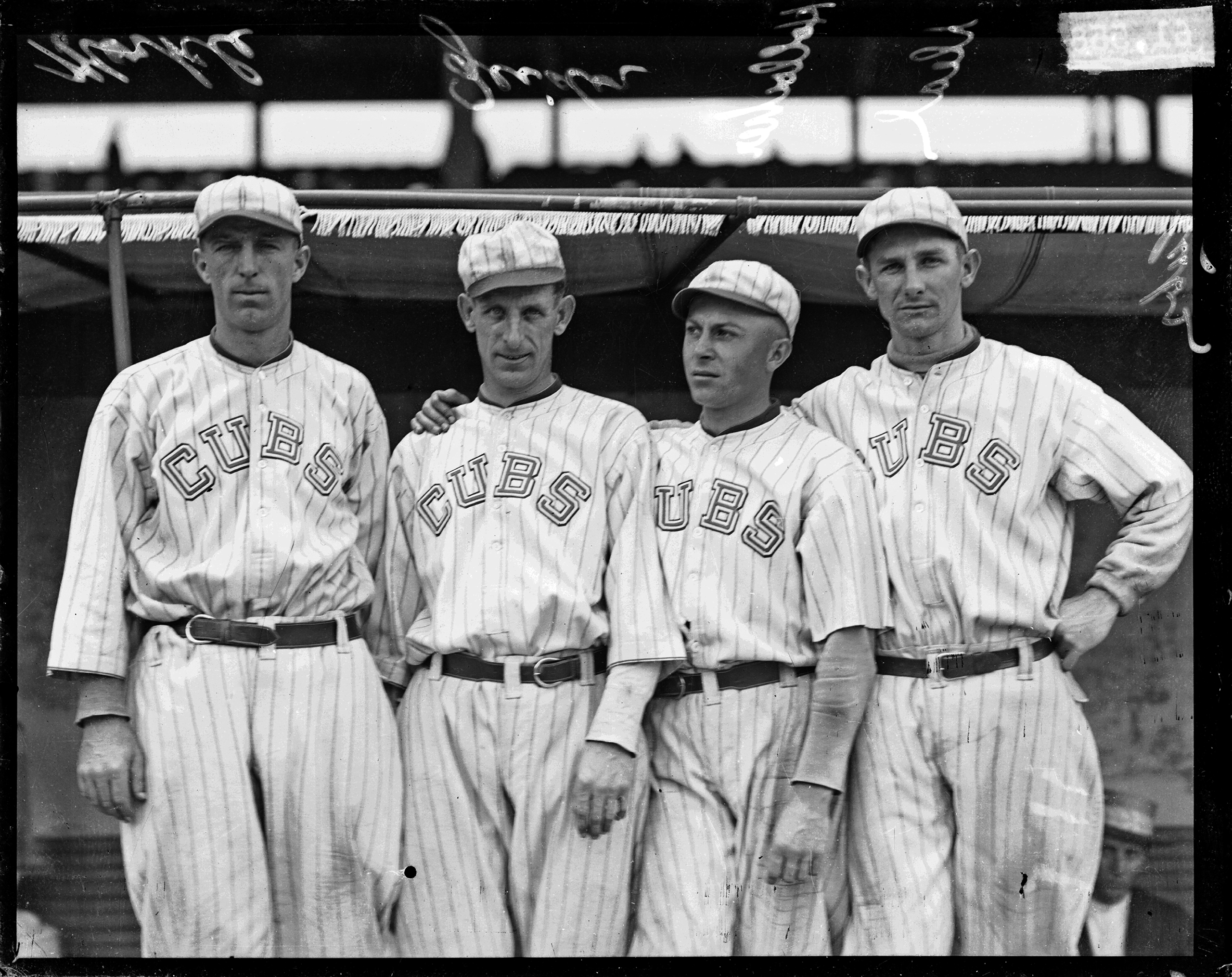 Chicago Cubs baseball players Merkle, Zeider, Charles Hollocher, and Deal standing in front of a dugout at Weeghman Park, Chicago, 1918.
