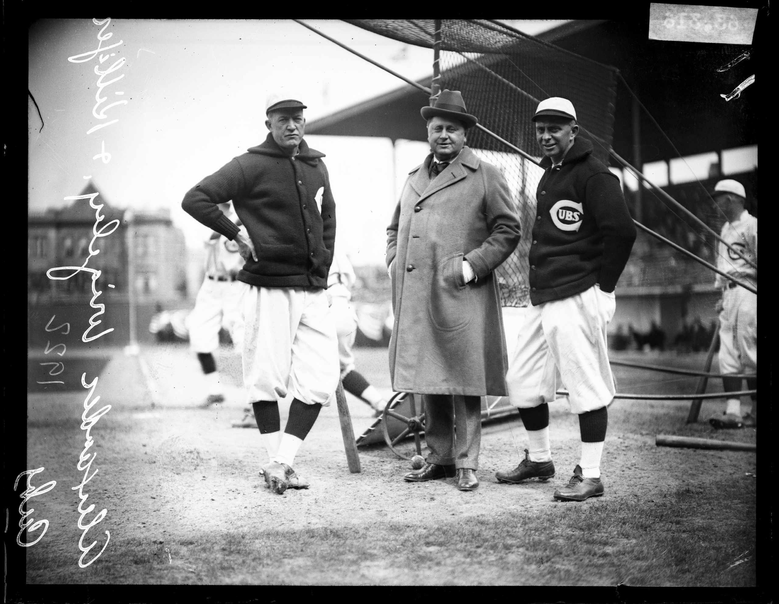 Left to right: Chicago Cubs baseball player Alexander, co-owner William Wrigley Jr, and manager Bill Killefer standing behind a batting practice backstop on the field at Weeghman Park, located at 1060 West Addison Street, Chicago, 1922.