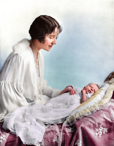 Elizabeth, Duchess of York (1900 - 2002), looking at her first child, future Queen, Princess Elizabeth. May 1926.