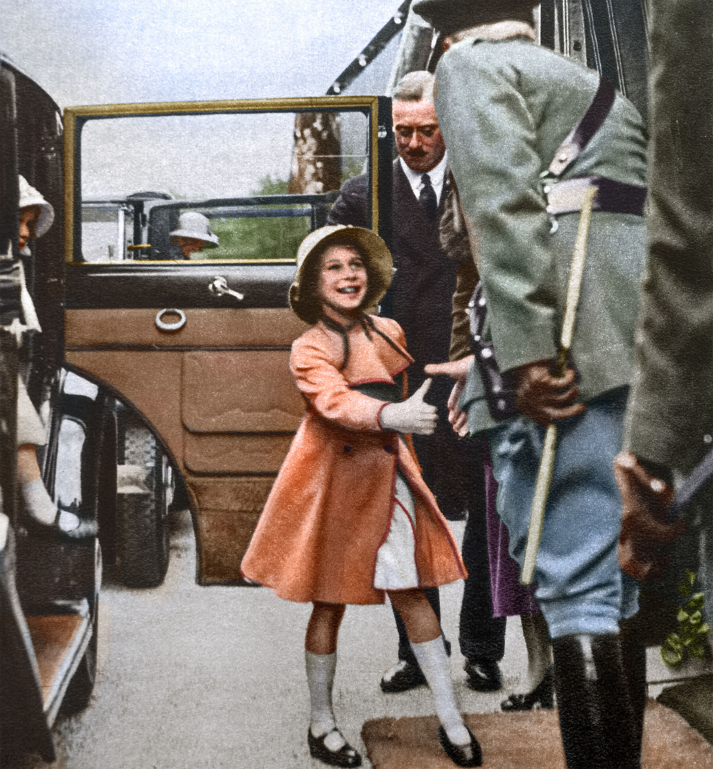 The Duchess of York took the children to see a daylight dress rehearsal of the Aldershot Tattoo. Here Princess Elizabeth greets the officer of the guard while Princess Margaret alights from the car at Rushmoor Arena. January 1935.