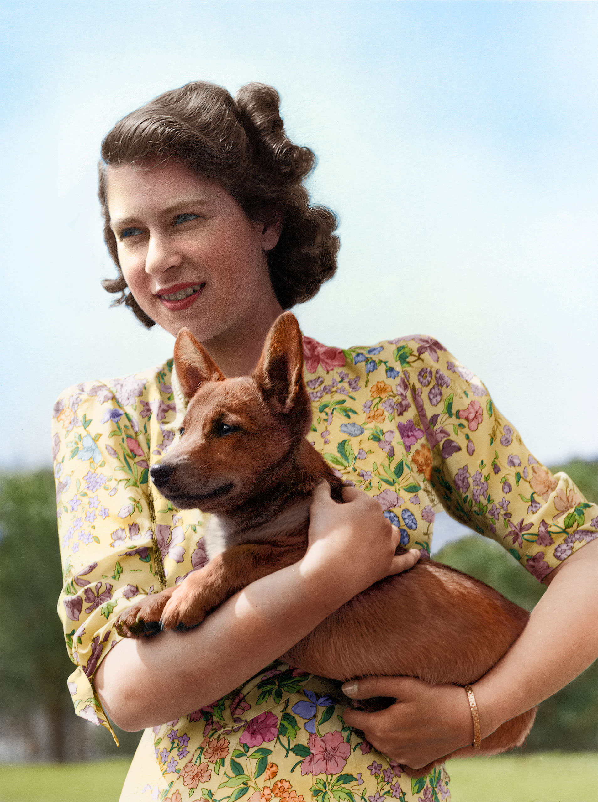 Princess Elizabeth holding Sue, a corgi pup, in the grounds of Windsor Castle, Berkshire, May 30, 1944.