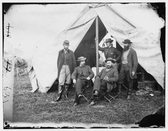 Detective Allan Pinkerton (sitting on the right) at Antietam during the Civil War. Standing behind Pinkerton holding the tent pole is believed to be Kate Warne, the first female detective in America, dressed as a man.