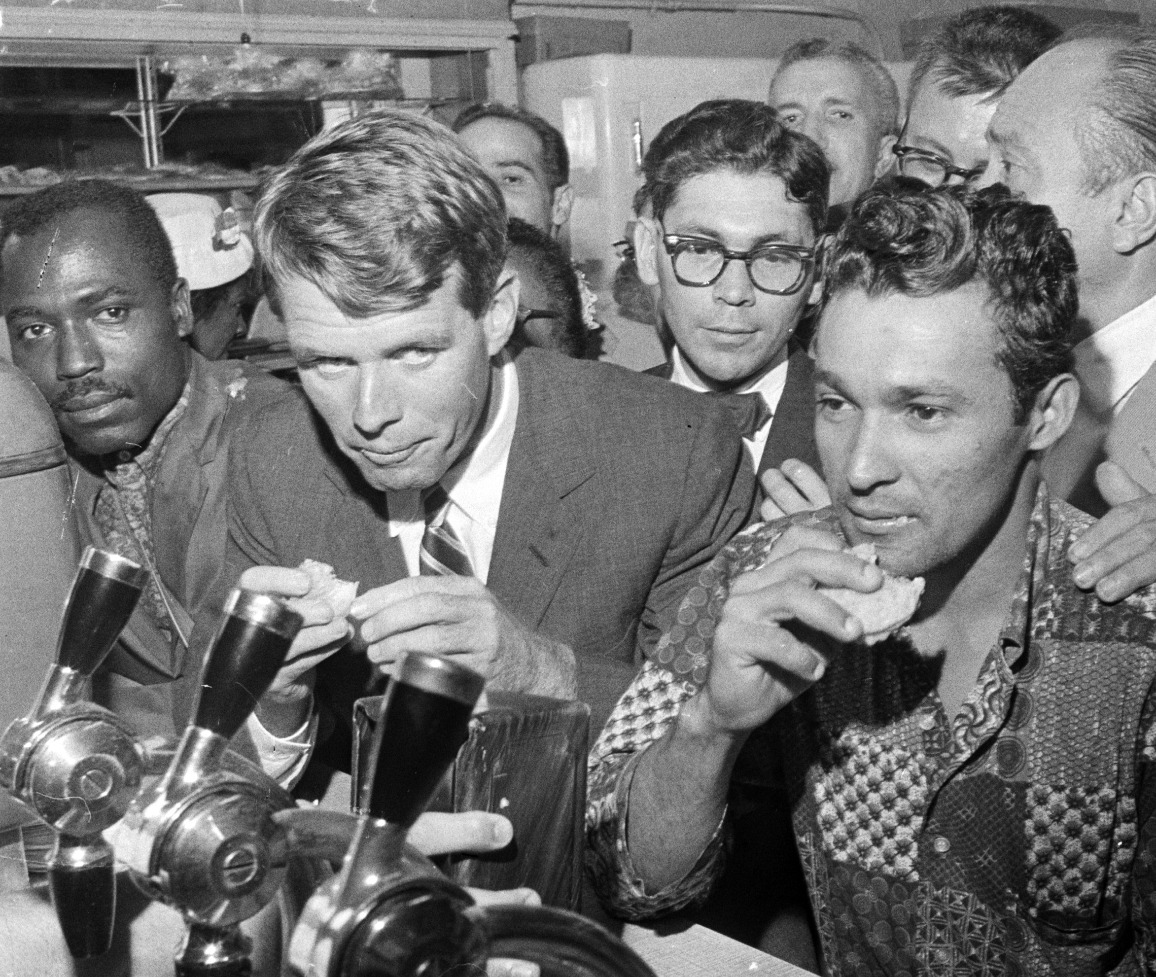 Robert Kennedy, managing his brother's presidential campaign, stops for a snack at a restaurant in Spanish Harlem. August 25, 1960.