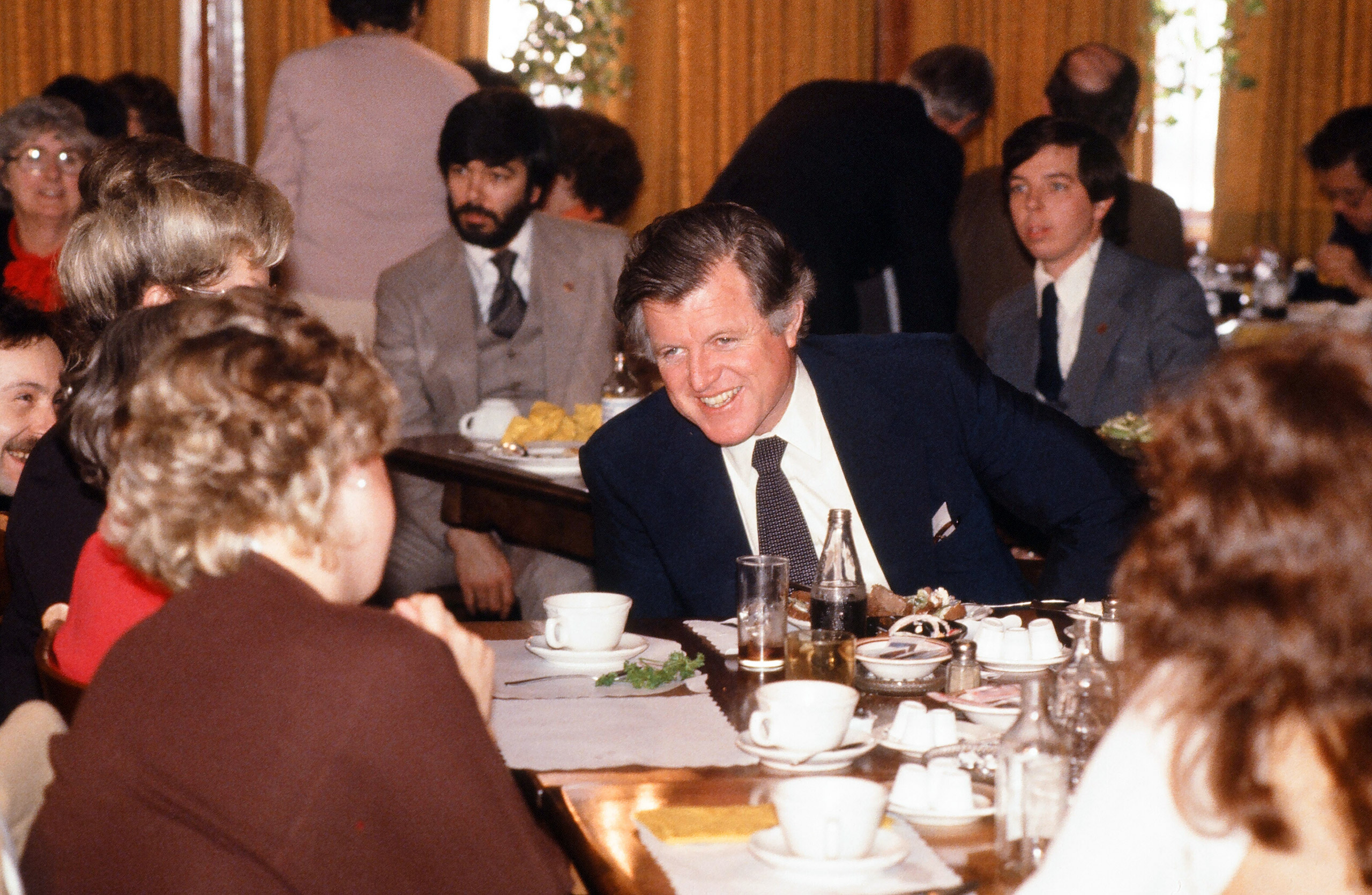 Senator Ted Kennedy laughs as he shares a meal with unidentified supporters at a restaurant during his campaign tour for the Democratic nomination for president, 1980.