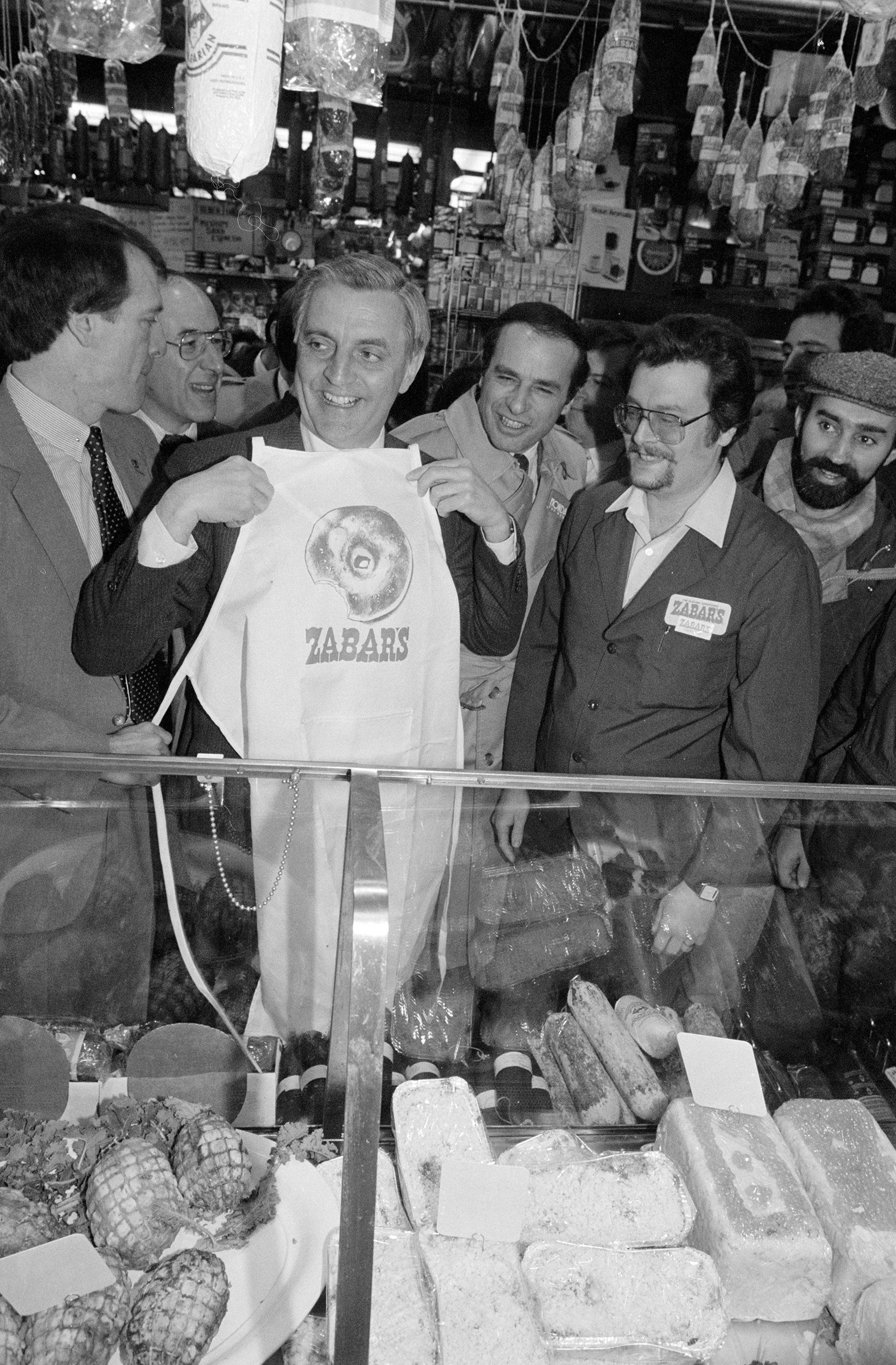 Former Vice President Walter Mondale holds an apron bearing an image of a bagel-presented to him during a visit to Zabar's Deli, campaigning for the Democratic presidential nomination. March 25, 1984.