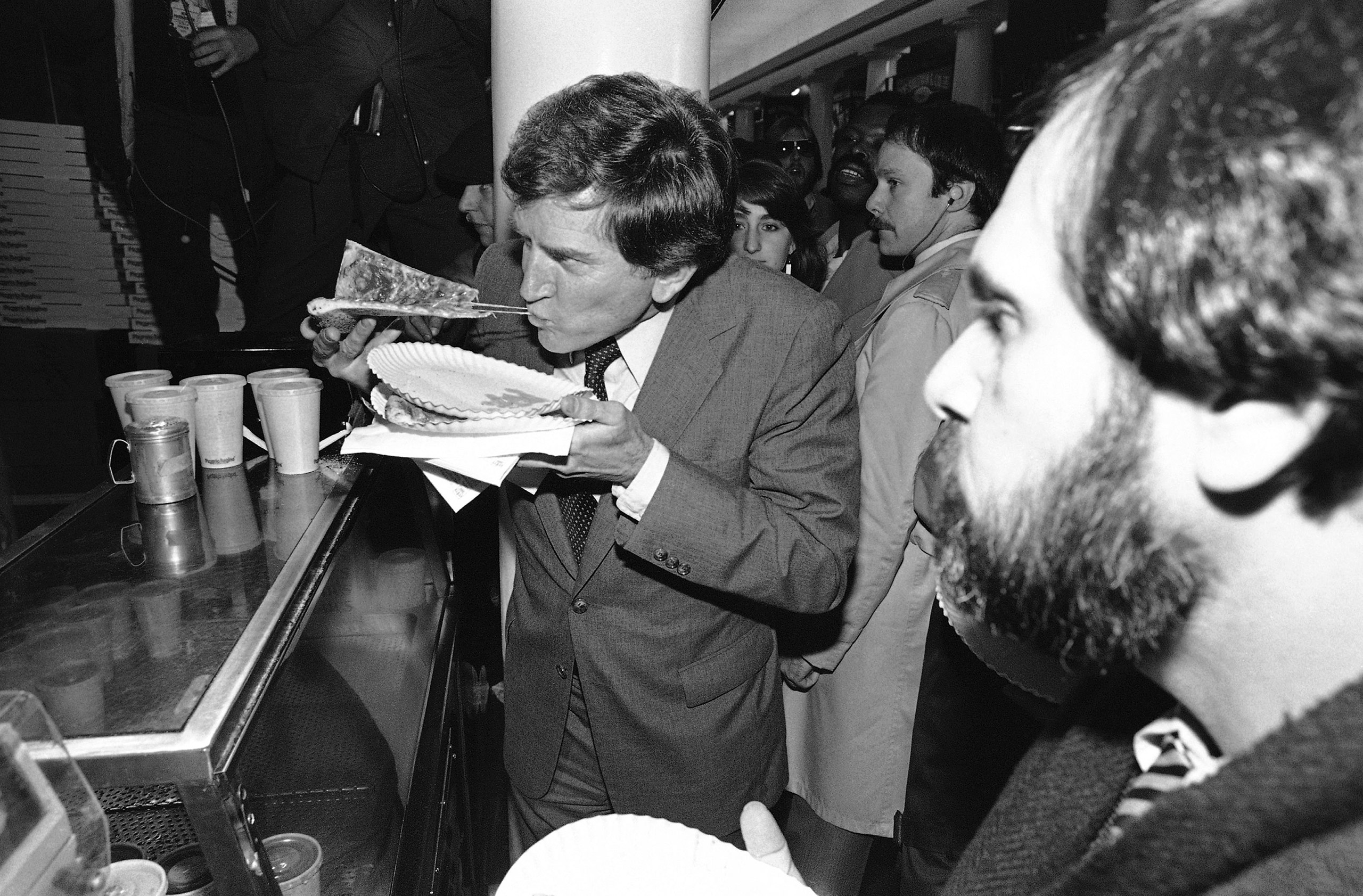 Sen. Gary Hart bites into a slice of pizza while on the campaign trail in Boston's historic Faneuil Hall district, March 5, 1984.