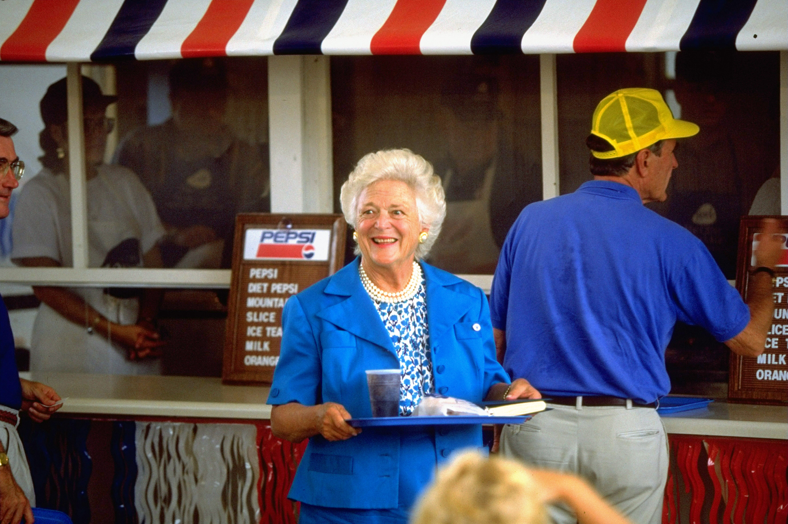 President George H.W. Bush and Barbara Bush patronizing food stand during campaign stop at state fair. Aug. 23, 1992.