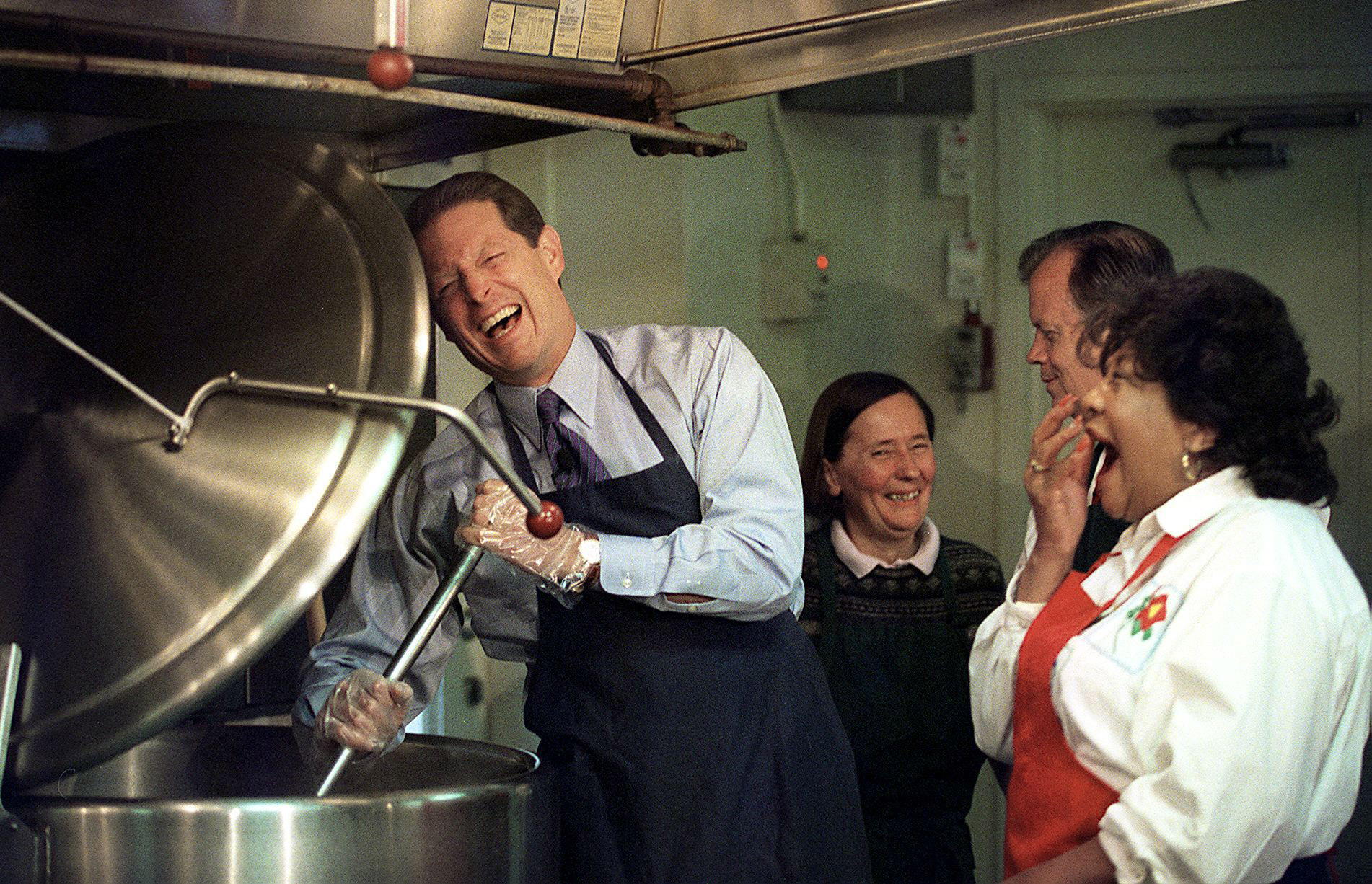 Vice President and presidential candidate Al Gore laughs as he stirs a vegetable stew as volunteer Veronica Park(2nd-L), Rep. Tony Hall, D-OH, and volunteer Olivia Ivy(R) look on during food preparation for the homeless as part of World Hunger Day Oct. 15, 1999, at Martha's Table in Washington, DC.