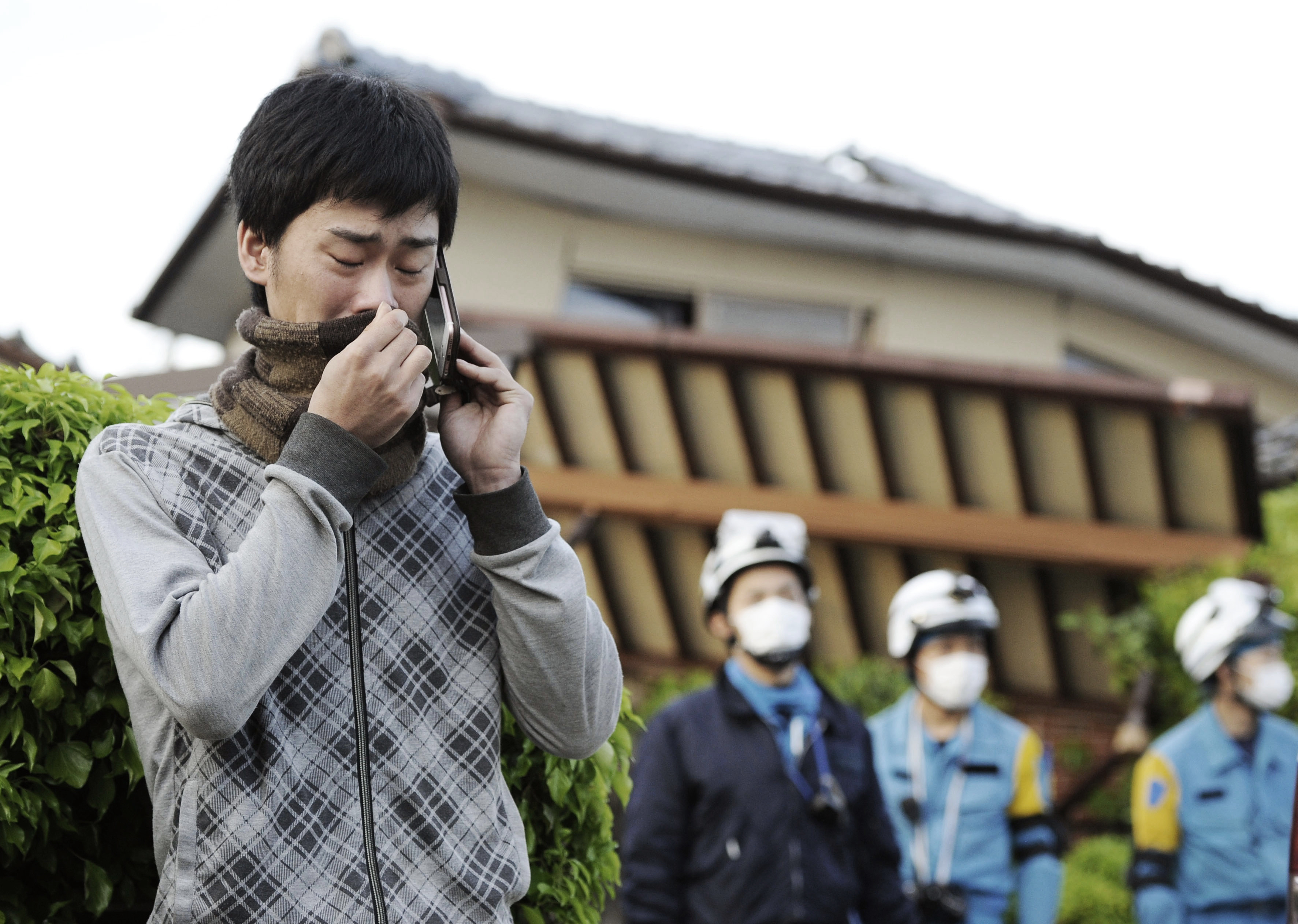 A man cries as he talks with his sister while an operation to rescue their father is continued in Mashiki, on April 16, 2016.