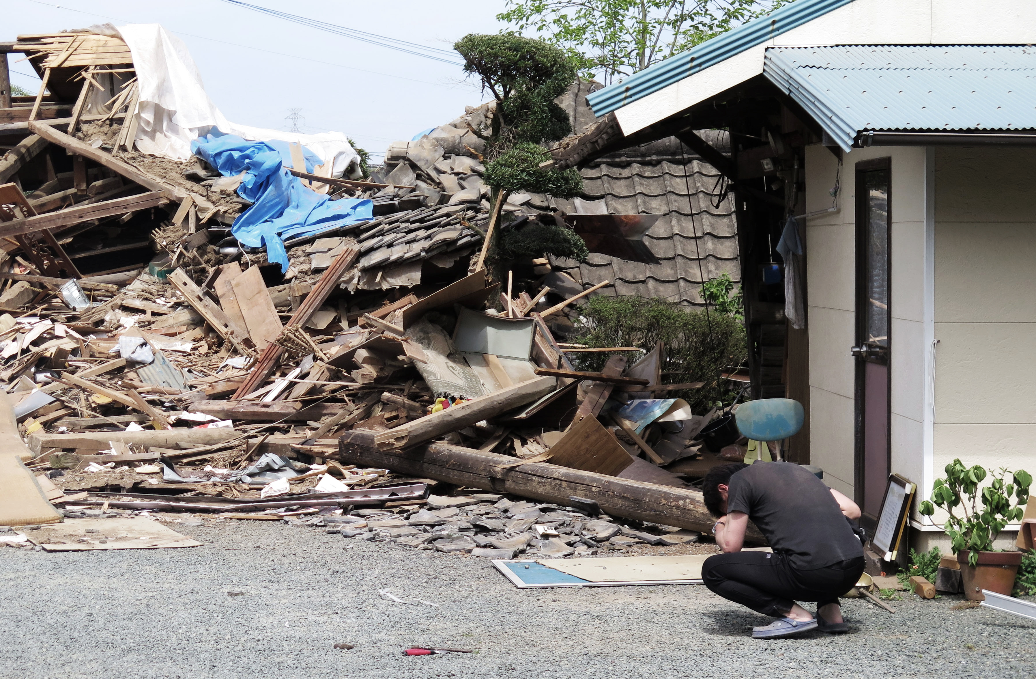 A man hunks down in front of a collapsed residence where his mother is being trapped after an earthquake in Mashiki, on April 16, 2016.