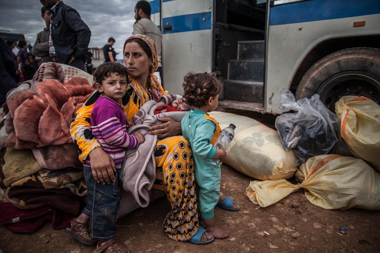 A Syrian Kurdish family waits to be taken to a Turkish shelter after fleeing shelling in Yumurtalik, Turkey.