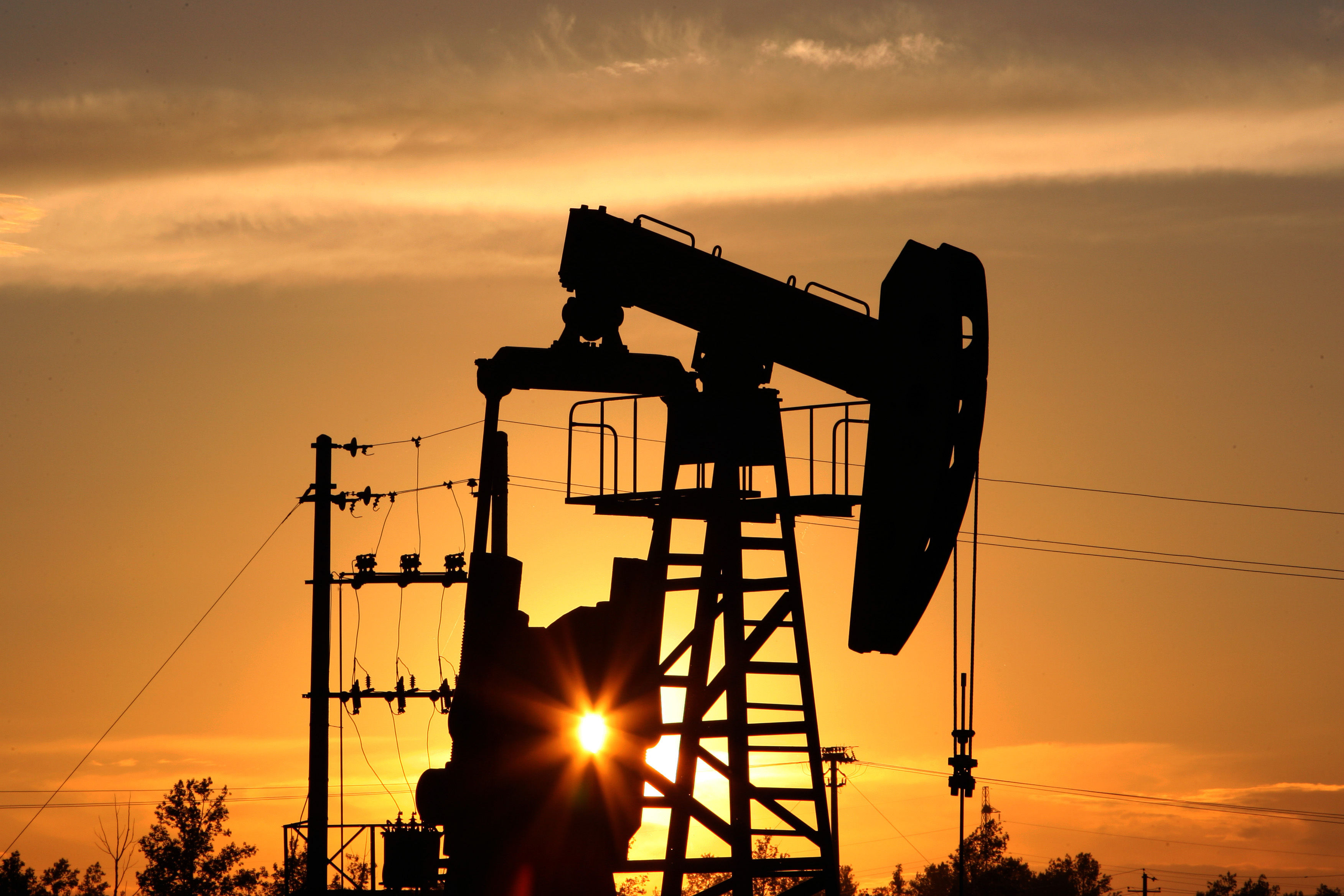 A CNPC 'nodding donkey' oil pump is seen at sunset in an oilfield outside Daqing, Heilongjiang province, China.