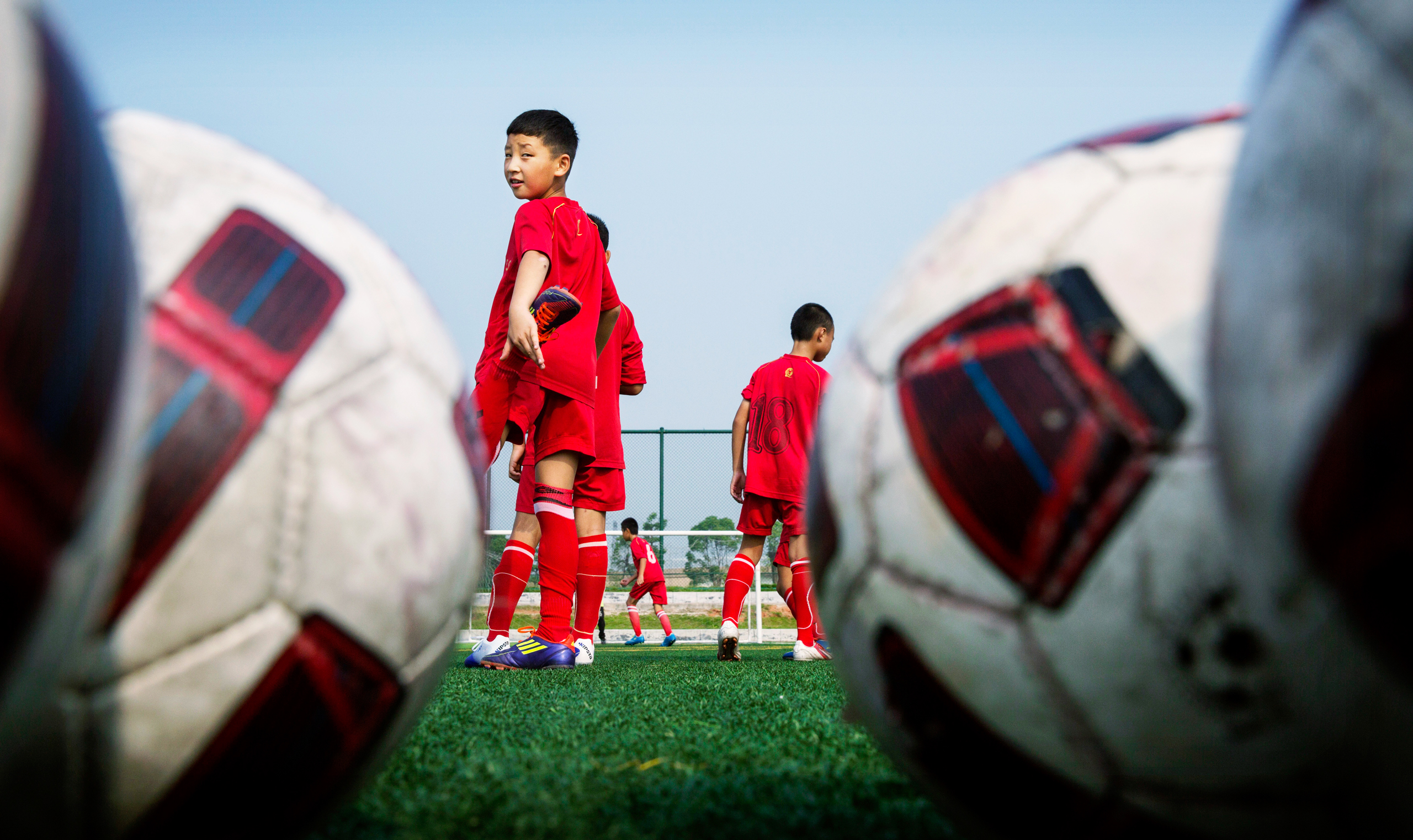 Chinese students wait their turn during training at the Evergrande Football School near Qingyuan